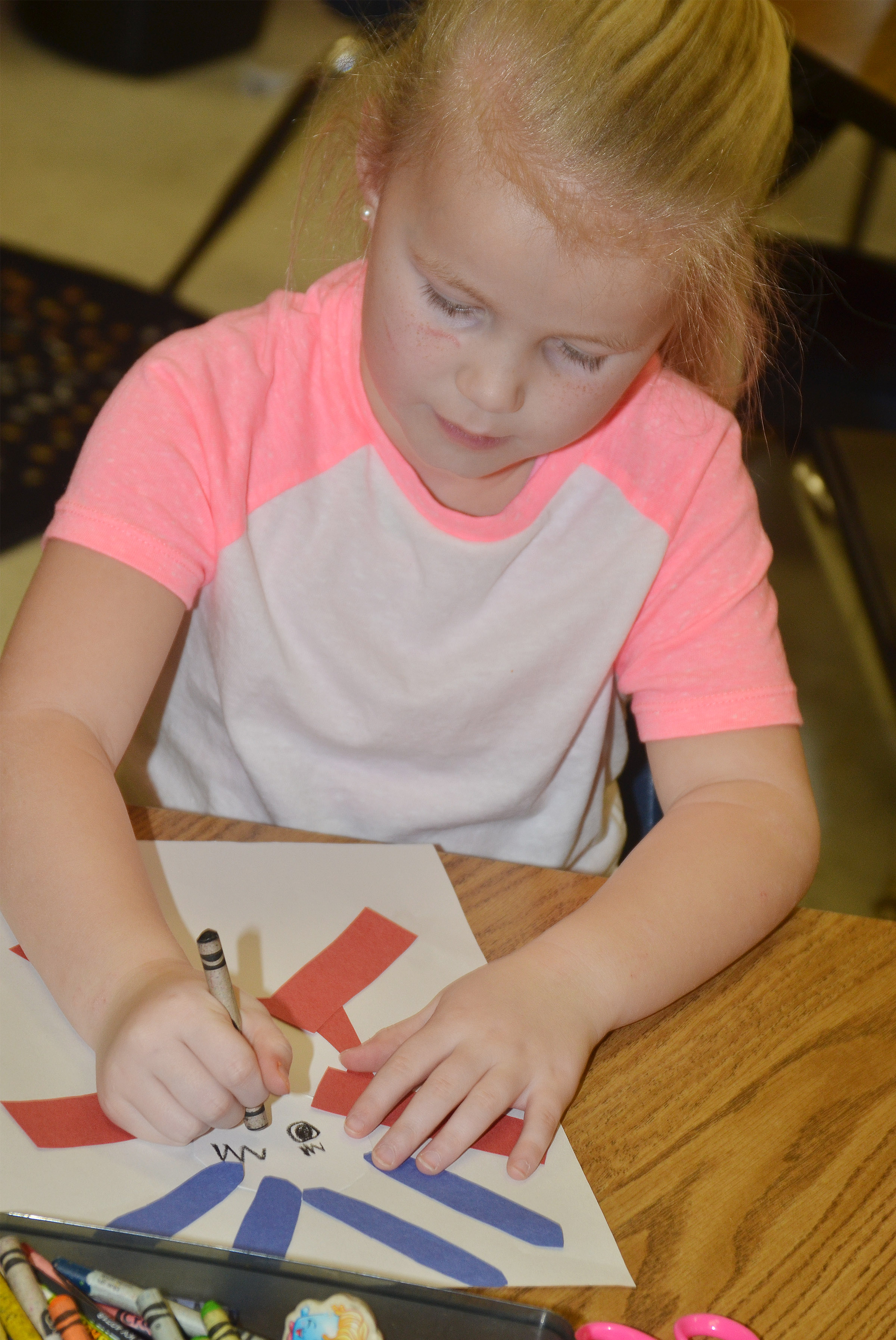 CES kindergartener Lillie Judd draws a face on her Thing 1 character.