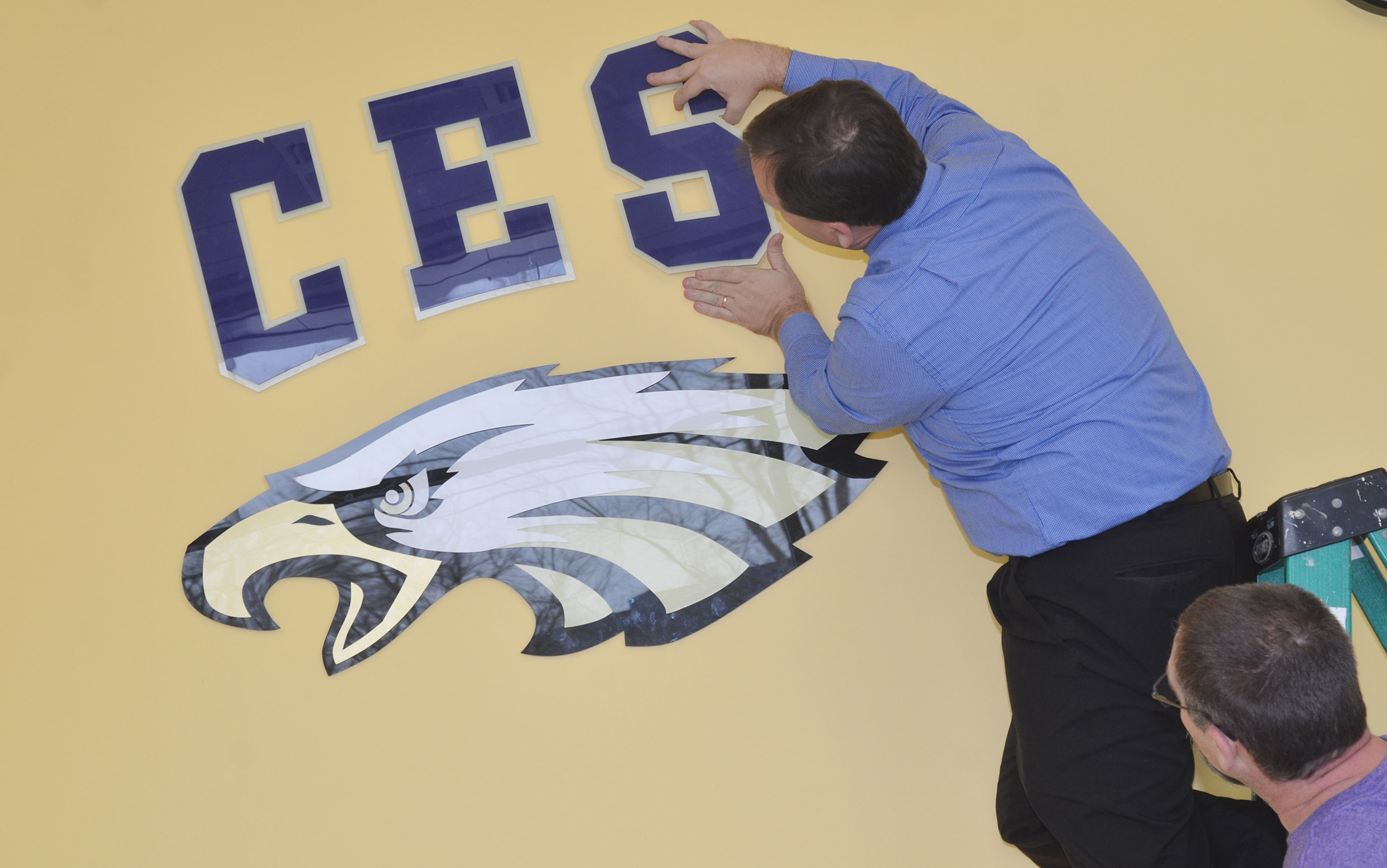 CES Principal Ricky Hunt, at left, and maintenance worker Randy Bricken Jr. install the CES letters and eagle.