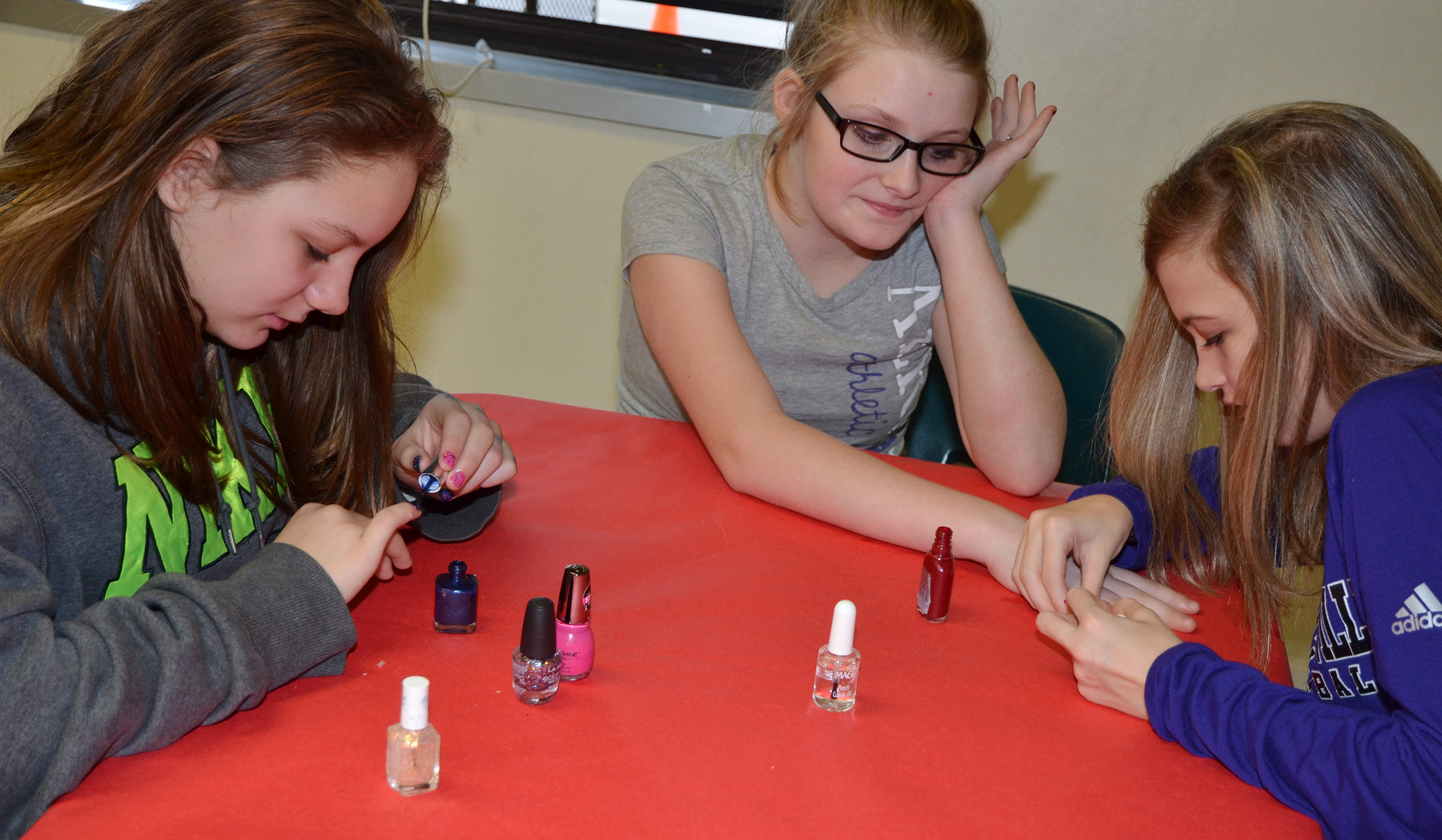 CMS eighth-grader Carly Adams, at right, paints Summer Jacobs's nails as fifth-grader Margaret Johnson paints her own nails.