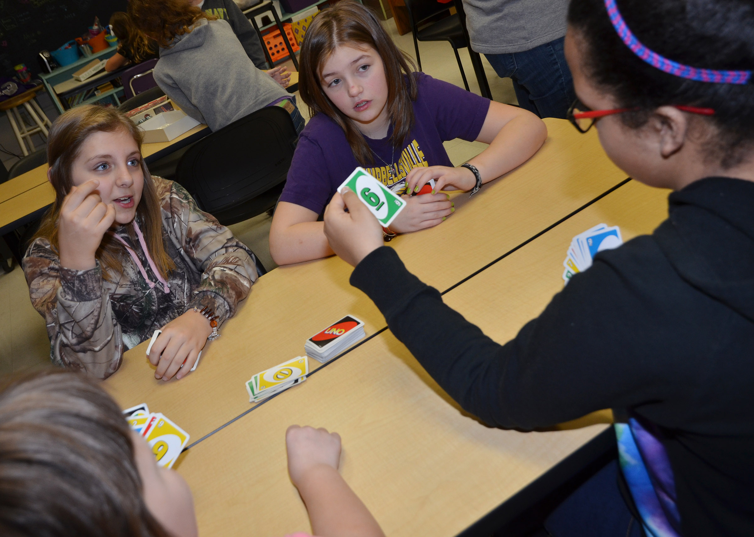 CMS fifth-graders Gracie Tungate, at left, and Angel Walker play Uno with their classmates.
