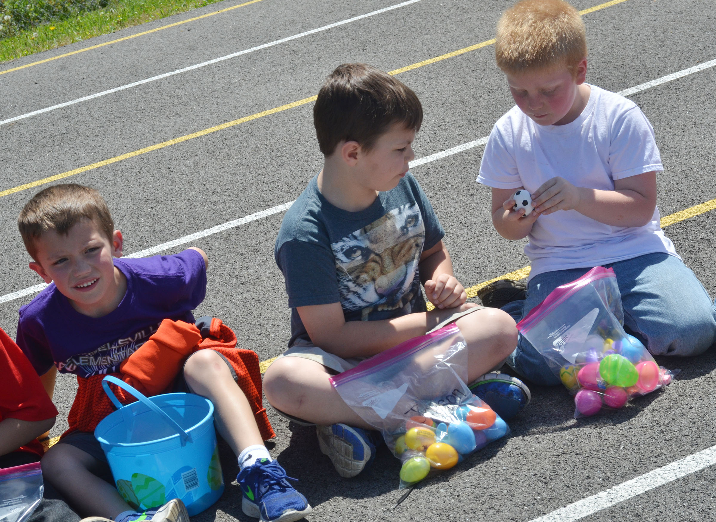 CES first-graders, from left, Owen Skaggs, Jaxson Hunt and Ben Parrott look inside their Easter eggs.