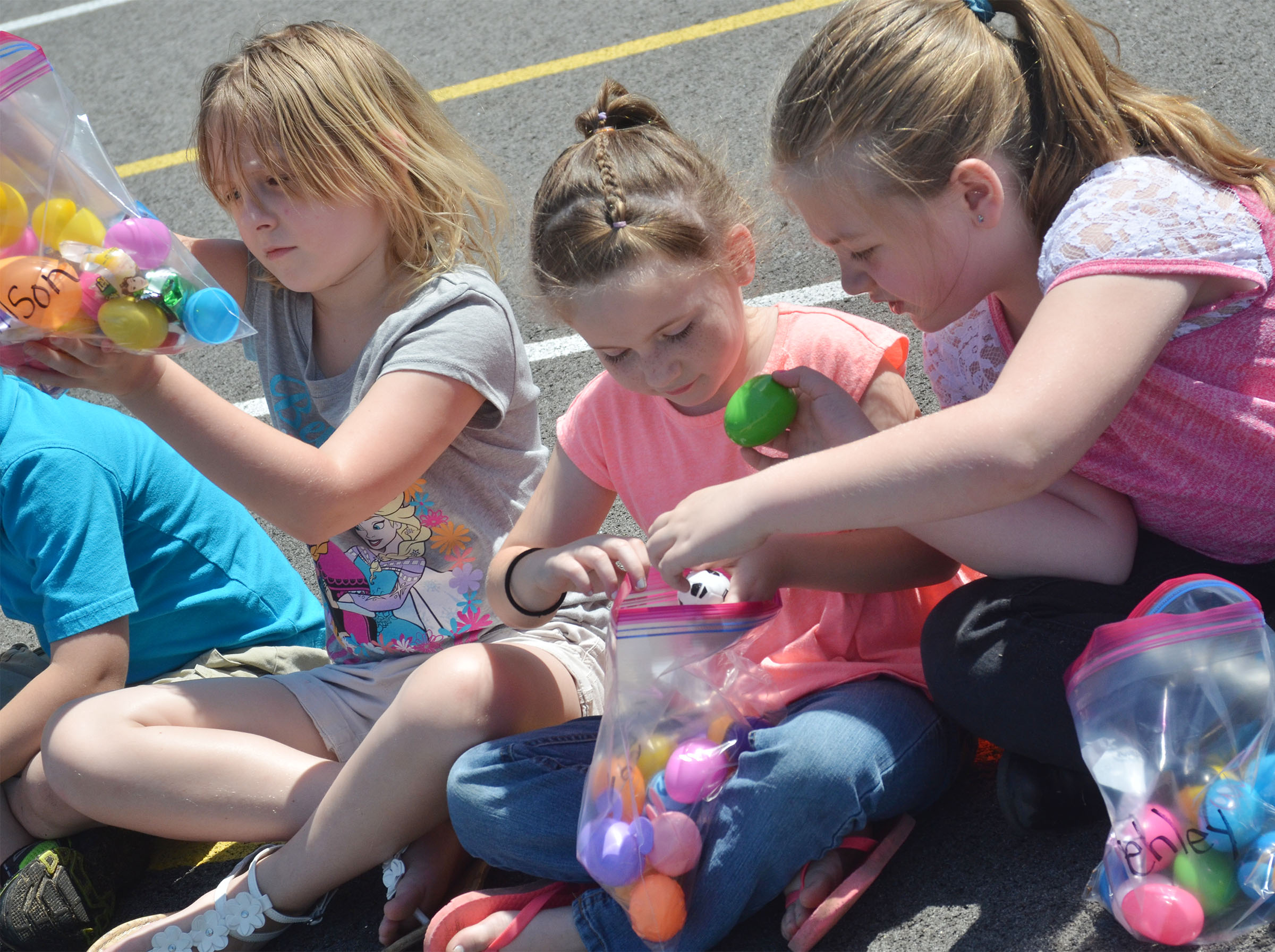 From left, CES first-graders Allison Dean, Kinsley Graham and Frehley Whitlow search through their Easter eggs to see what's inside.