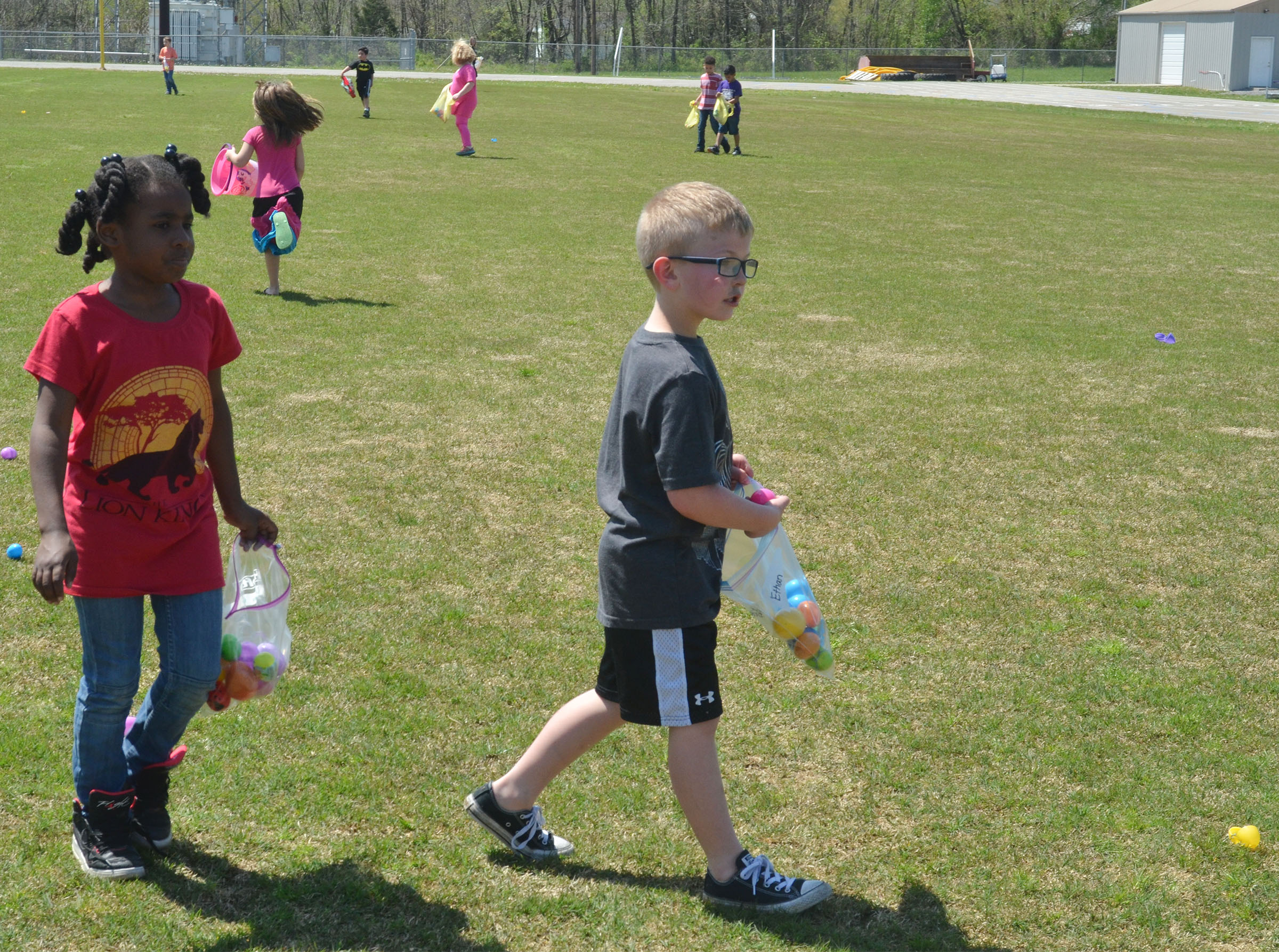 CES first-graders Destini Gholston, at left, and Ethan Bailey search for Easter eggs.