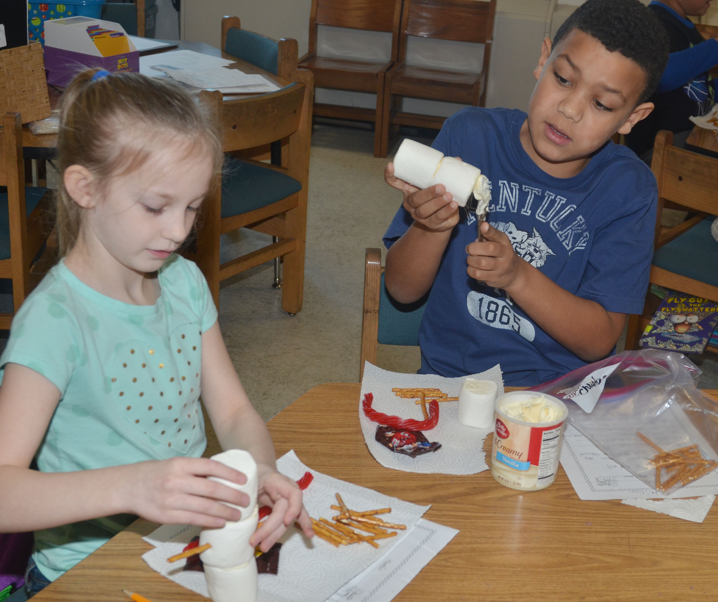 CES third-graders Kendall Bright, at left, and Christian Hart build their edible snowmen.