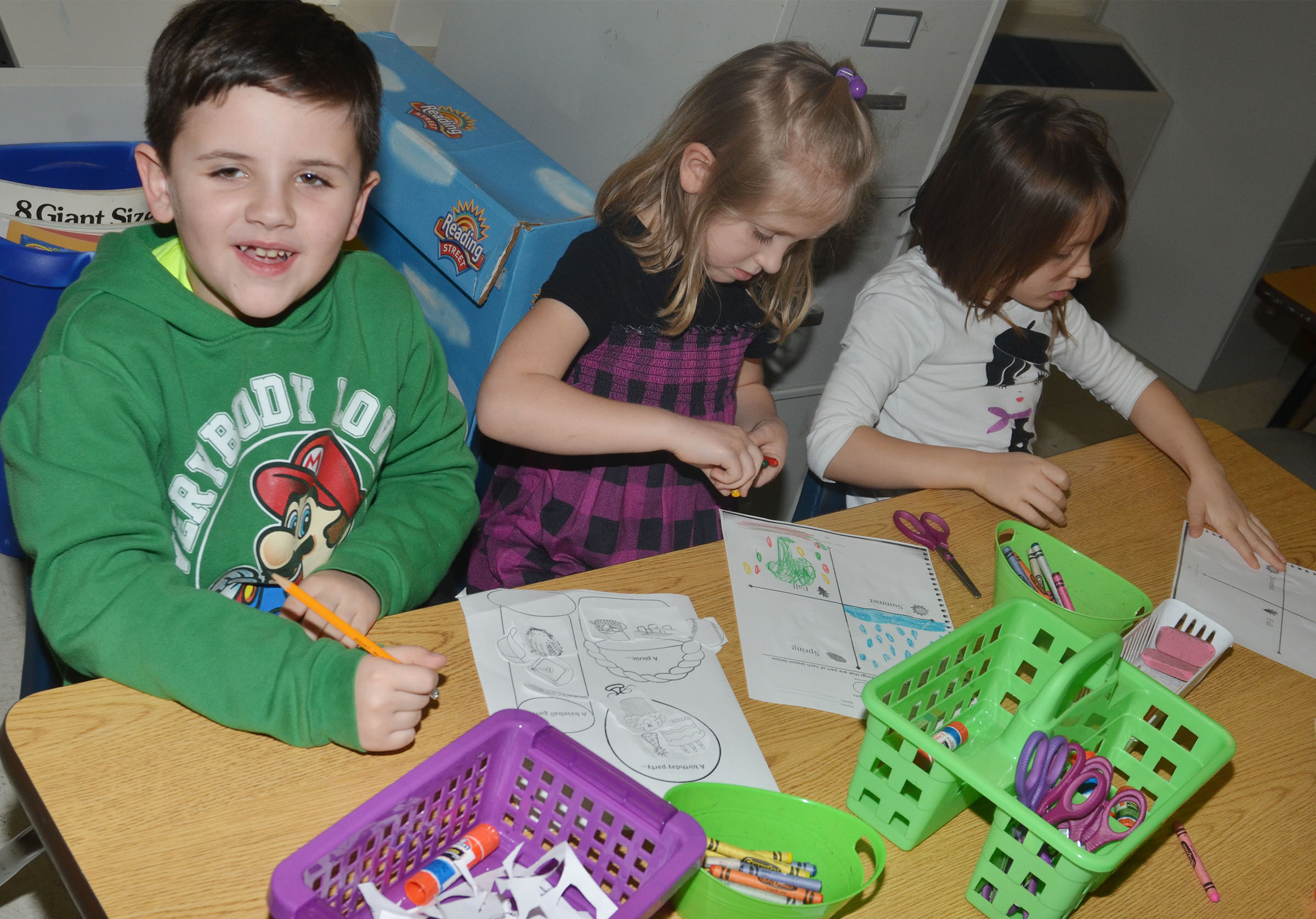 CES kindergarteners, from left, Casen Meredith, LeeAnna Garvin and Veda Burgess color their worksheets.