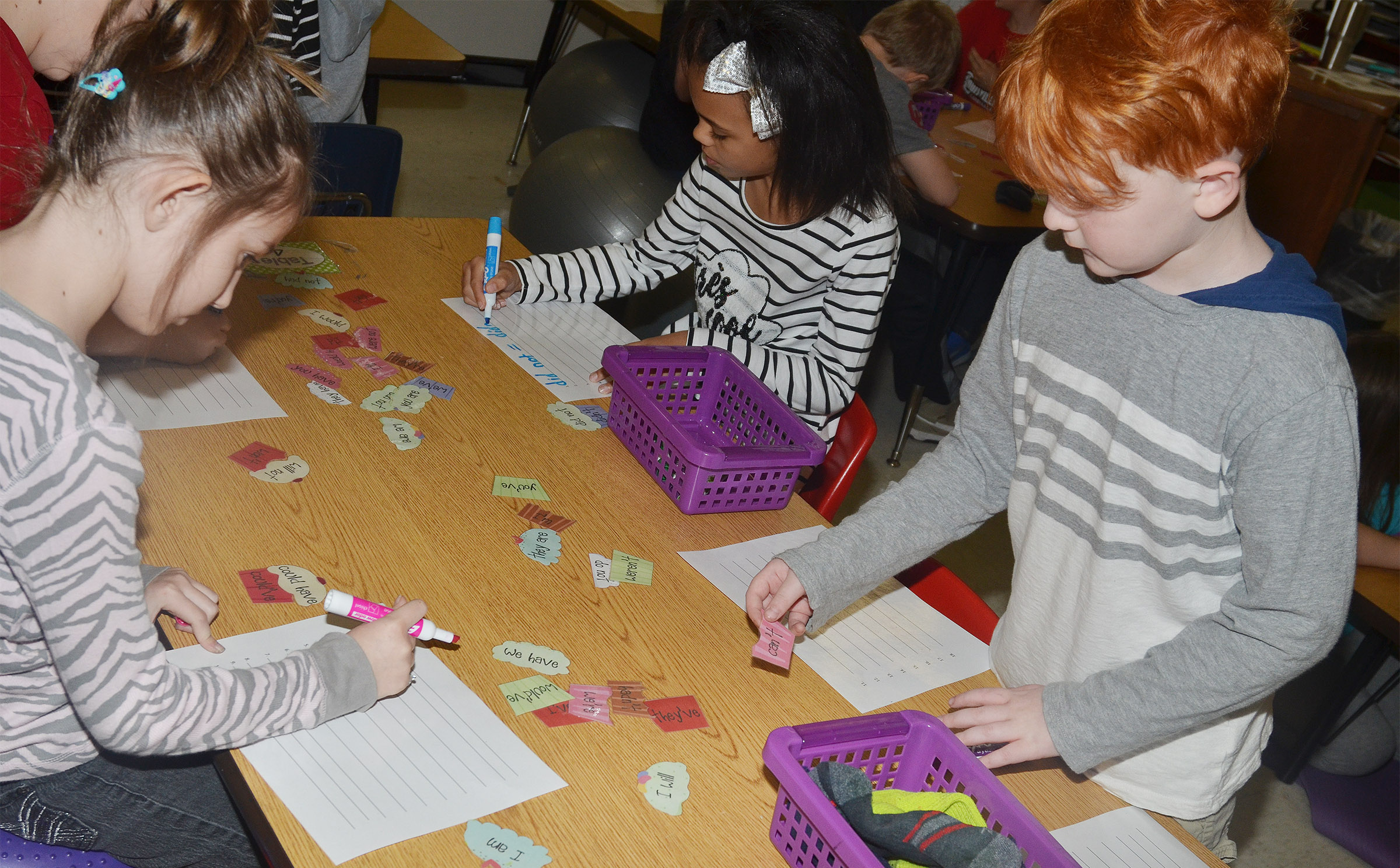 CES second-graders Braelyn Taylor, at left, and Gavin Martin play the contraction cupcake game.