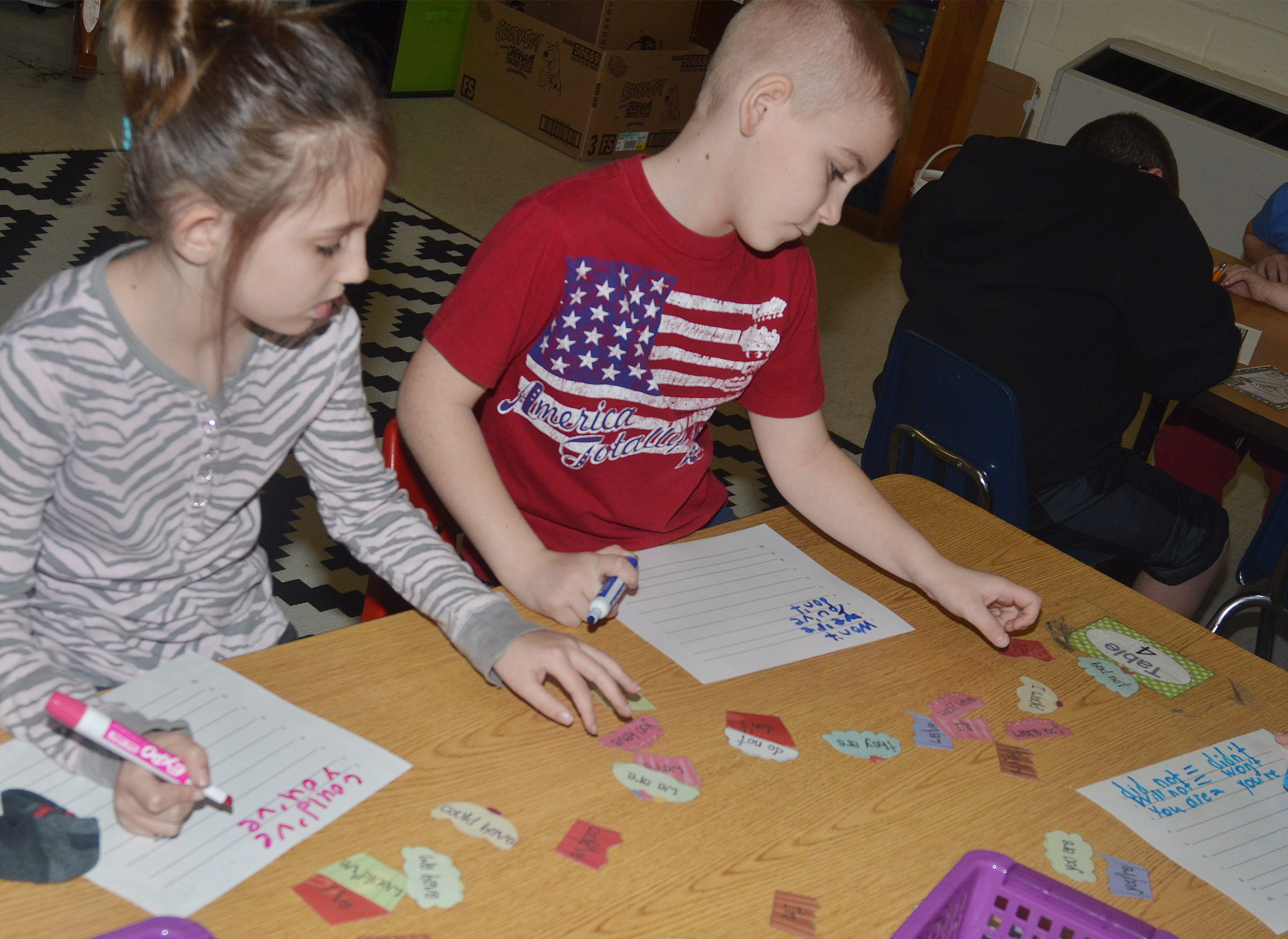 CES second-graders Kairi Tucker, at left, and Joseph Greer play the contraction cupcake game.