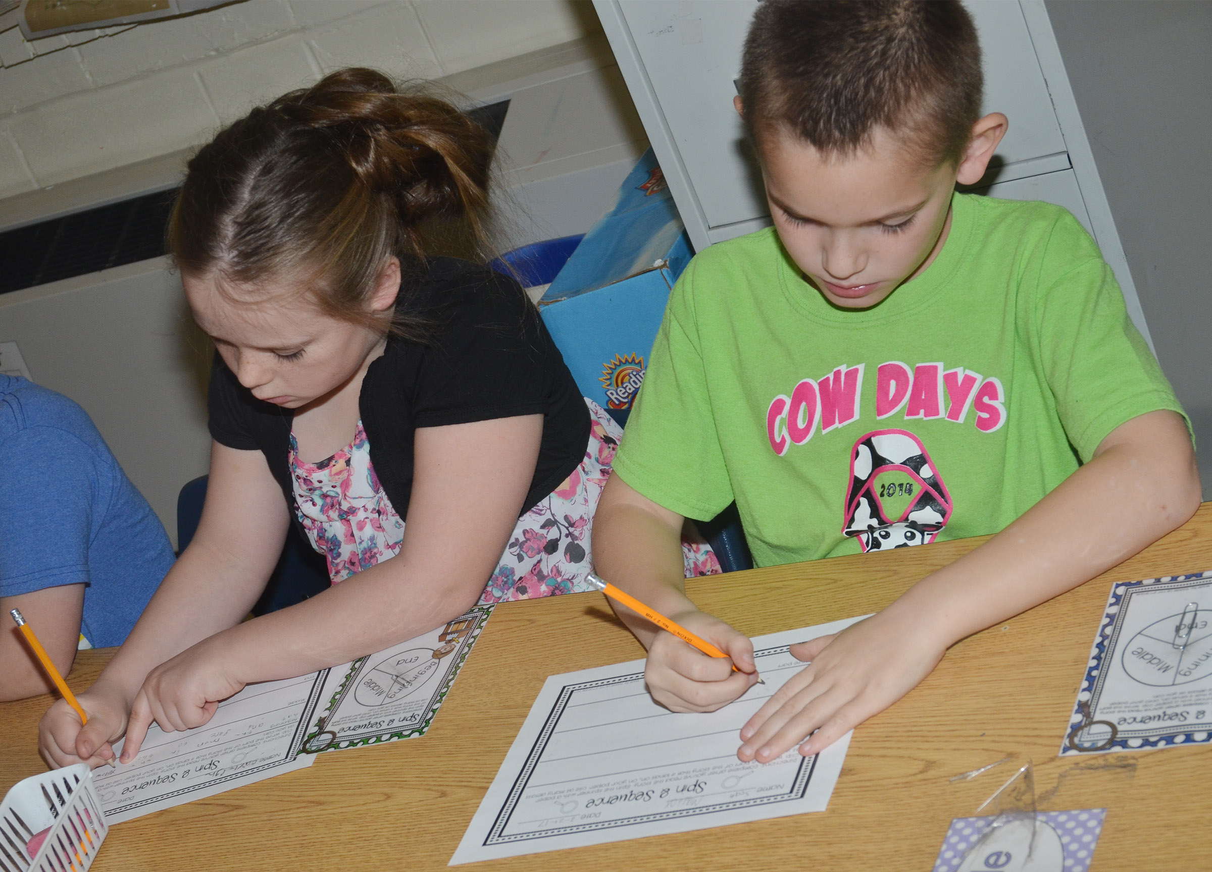 "CES second-graders Cayleigh Underwood, at left, and Sean Welch write about their favorite part of ""Curious George Goes to the Chocolate Factory."""
