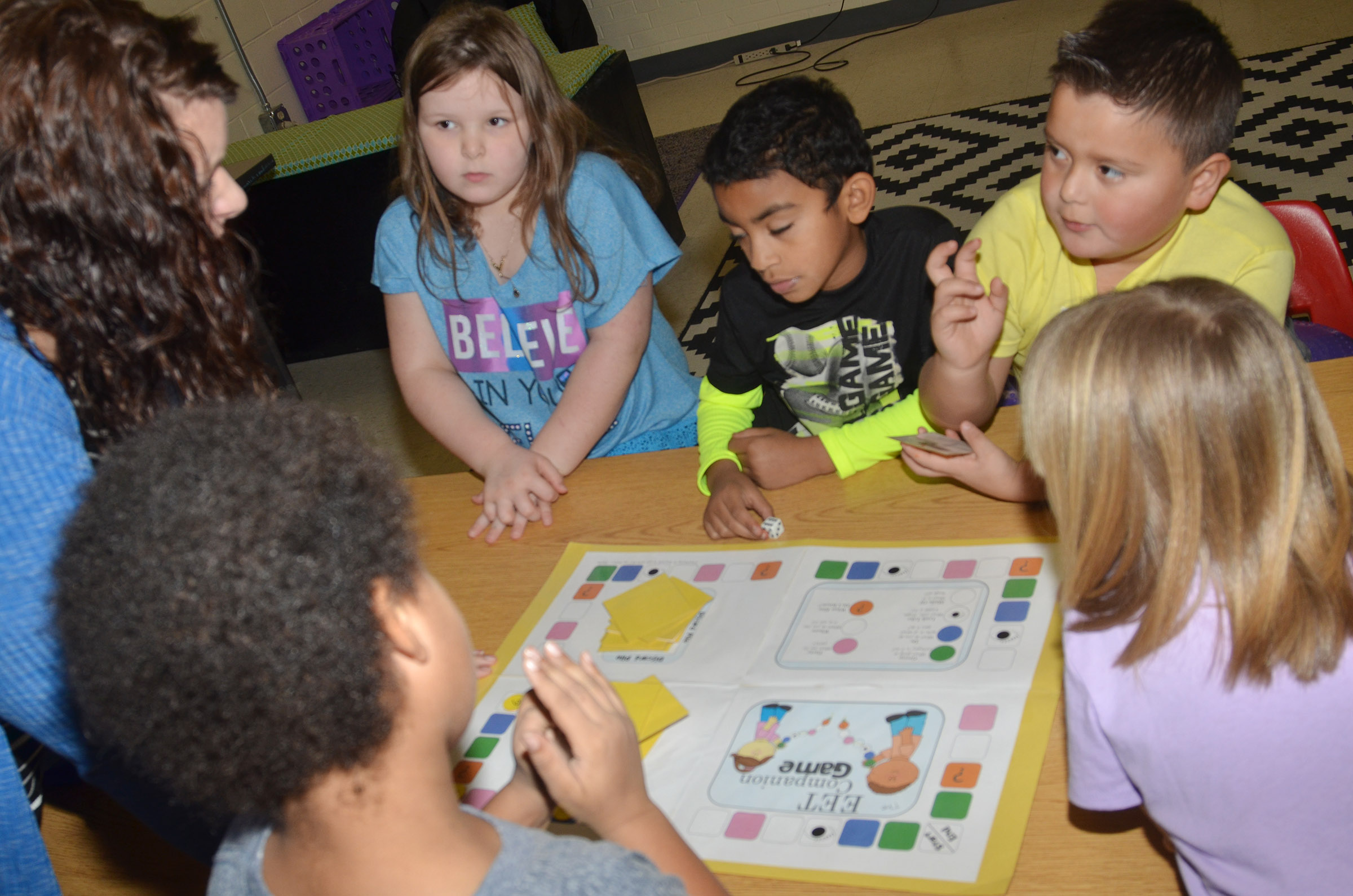 CES Explorers teacher Miriah Cox, at left, helps first-graders, from left, Kierra Maupin, Enoch Smith and Alex Mixtega, and their classmates, play a comprehension game.