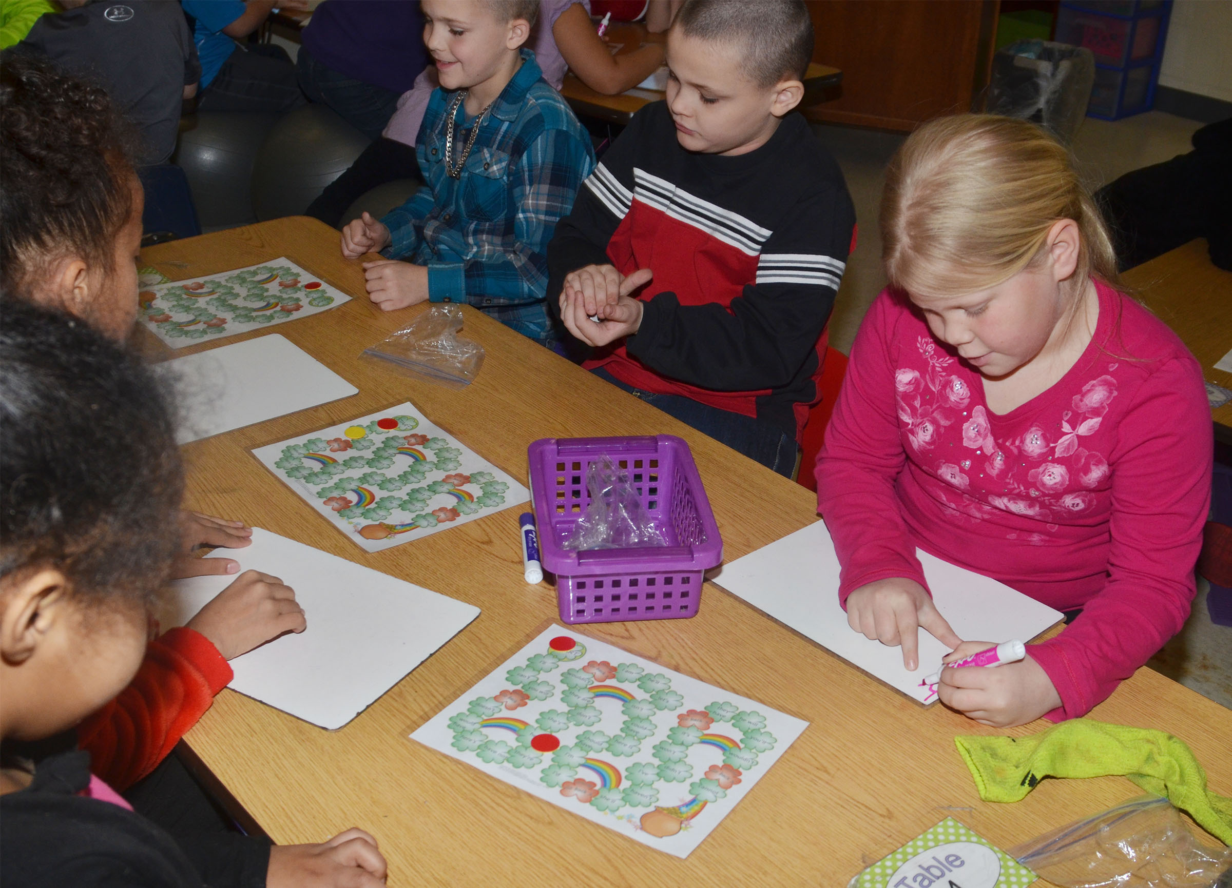 From left, CES second-graders Kadin Coppage, Aiden Dziabula and Lily Coots play the pot of gold game.