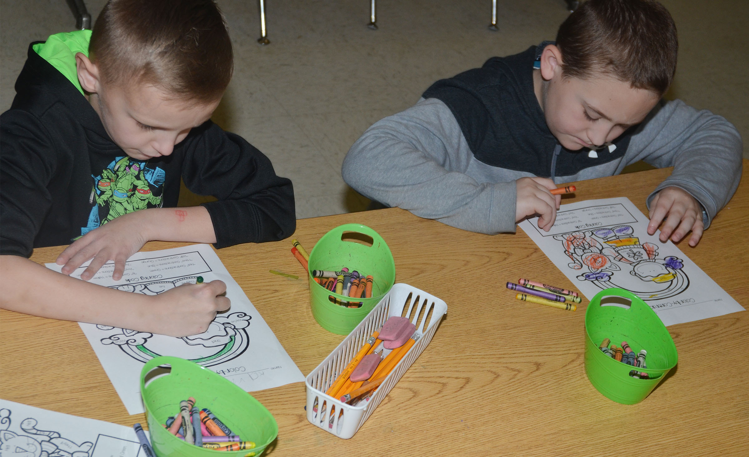 CES second-graders Aaron Ritchie, at left, and Carson Ford color their St. Patrick's Day scenes by using the key containing contractions and colors.