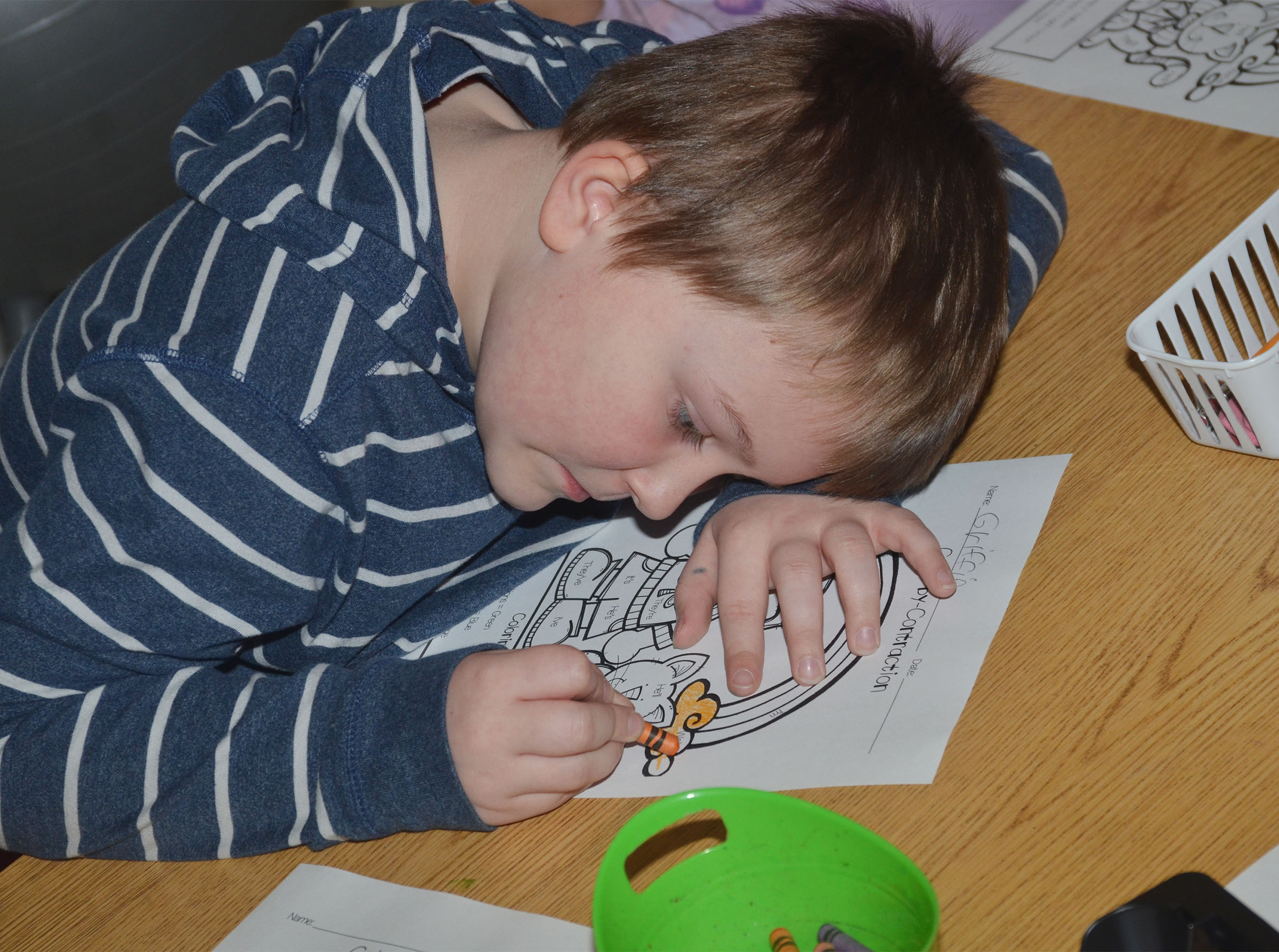 CES second-grader Griffin Skaggs colors a St. Patrick's Day scene using the key containing contractions and colors.