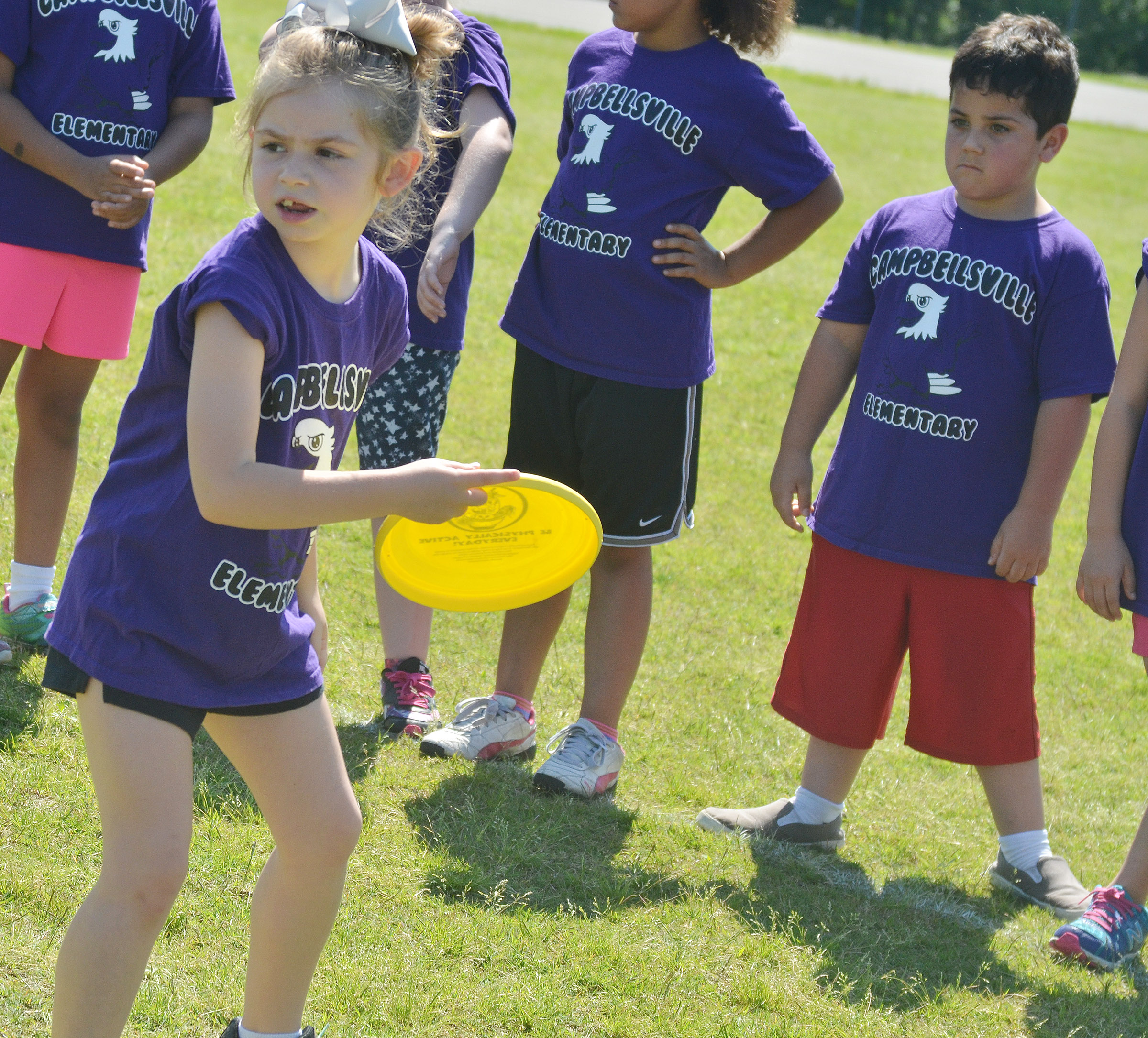 CES first-grader Lainey Price throws a Frisbee.