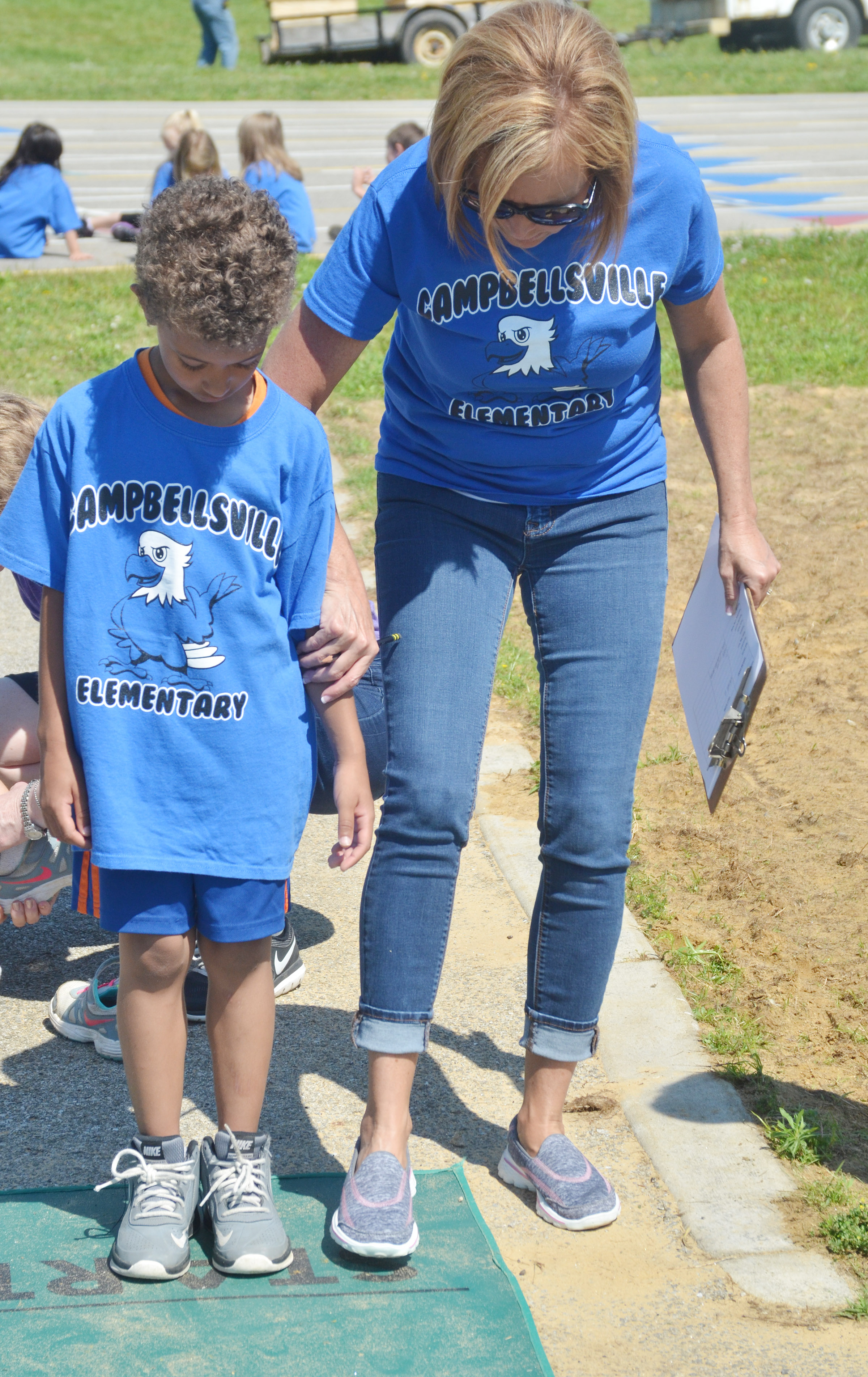 CES kindergarten teacher Lisa Wiseman helps Tyce Owens at the long jump.