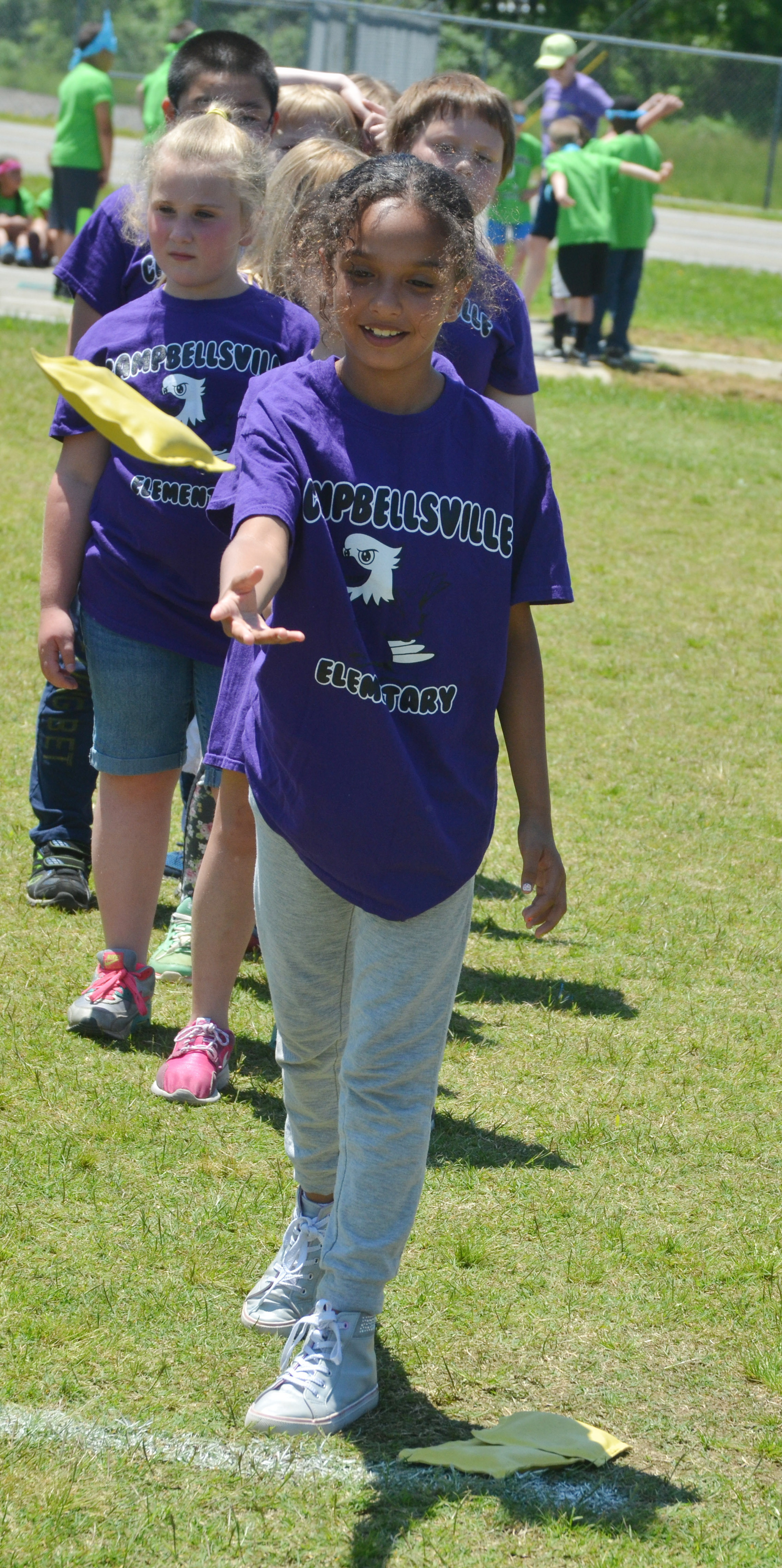 CES third-grader Alyssa Knezevic throws a bean bag.
