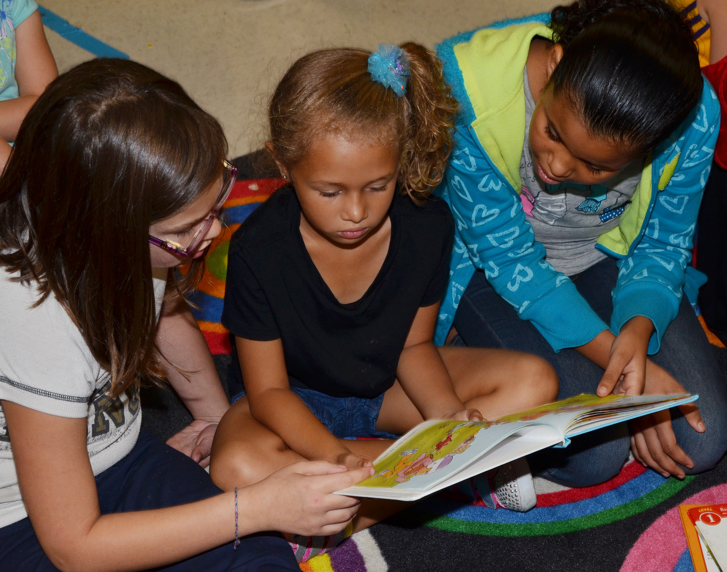 CES fifth-graders Destiny Milby, at left, and Kenya Bridgewater read to kindergartener Fallyn Smith.