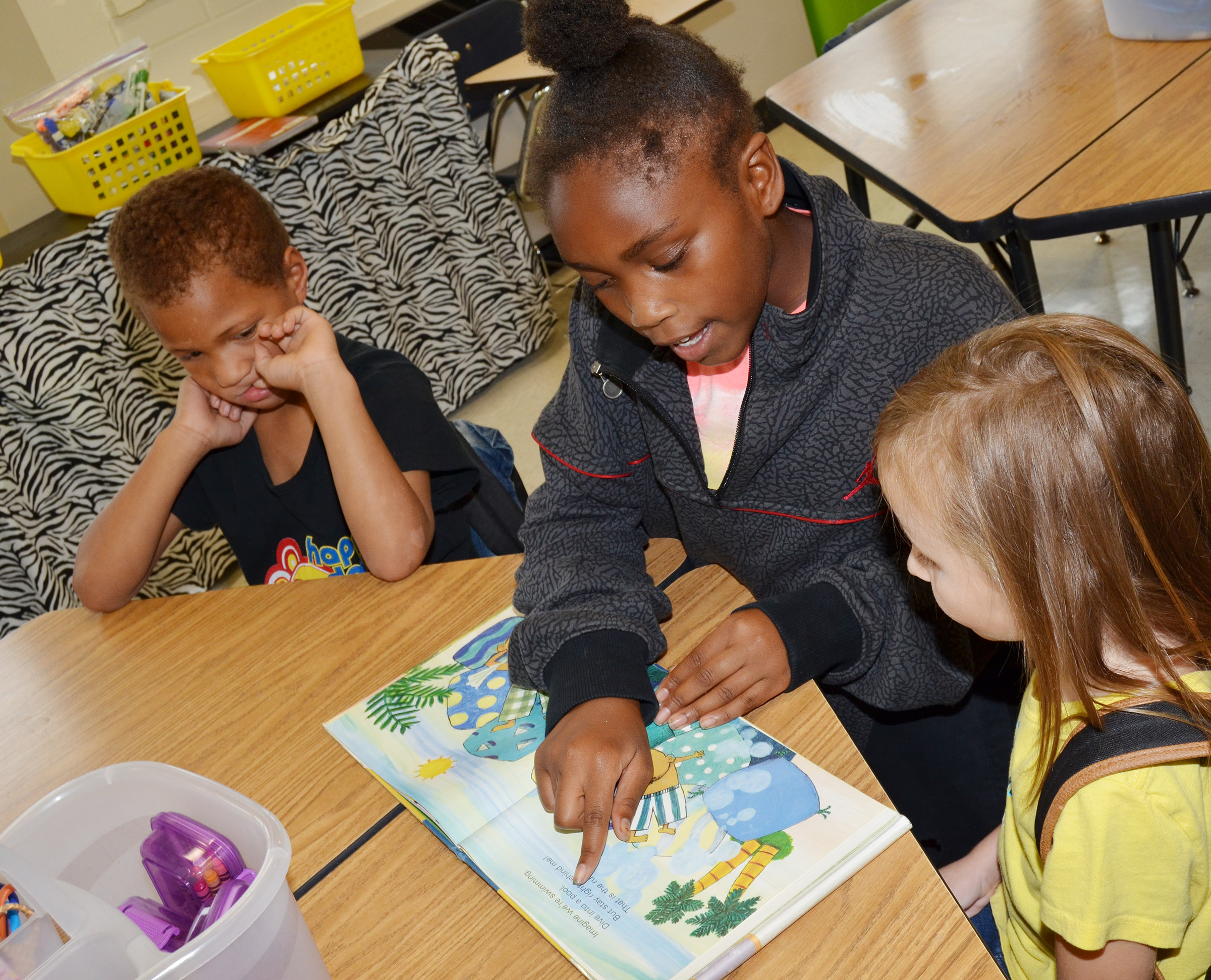 CES fifth-grader Ta'Zaria Owens reads to kindergarteners Jamerius Miller, at left, and Tabitha Leggett.