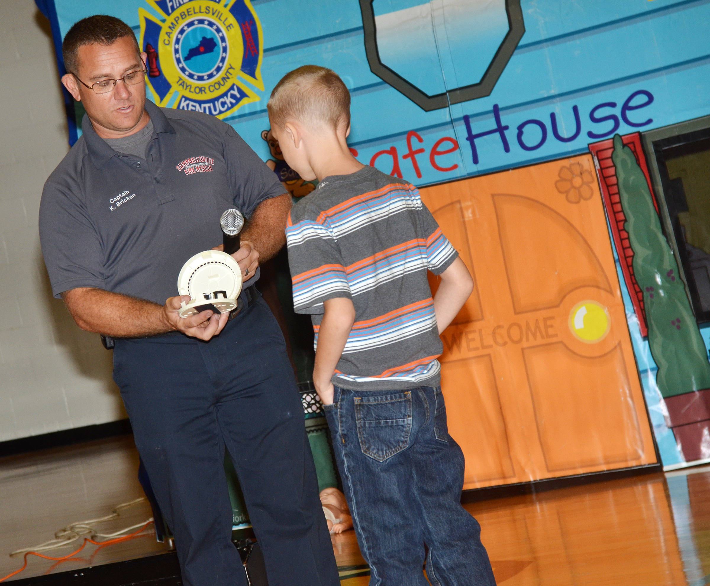Campbellsville Fire & Rescue Captain Keith Bricken checks the battery in a smoke detector, with help from CES third-grader Braxton Agee.