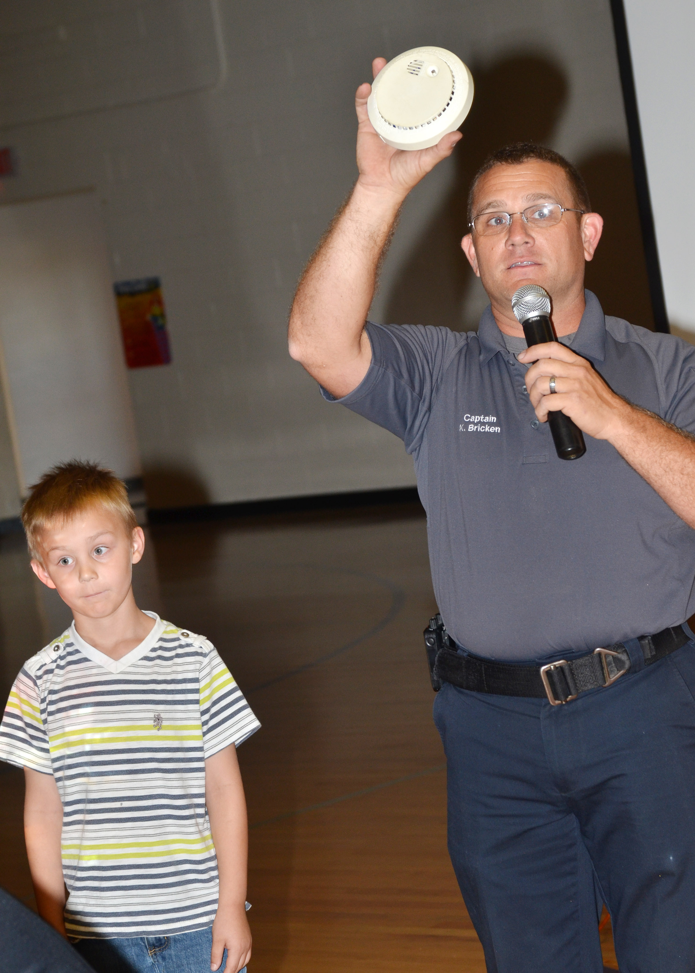 Campbellsville Fire & Rescue Captain Keith Bricken shows CES students how to check the battery in a smoke detector, with help from second-grader Hunter Bates.
