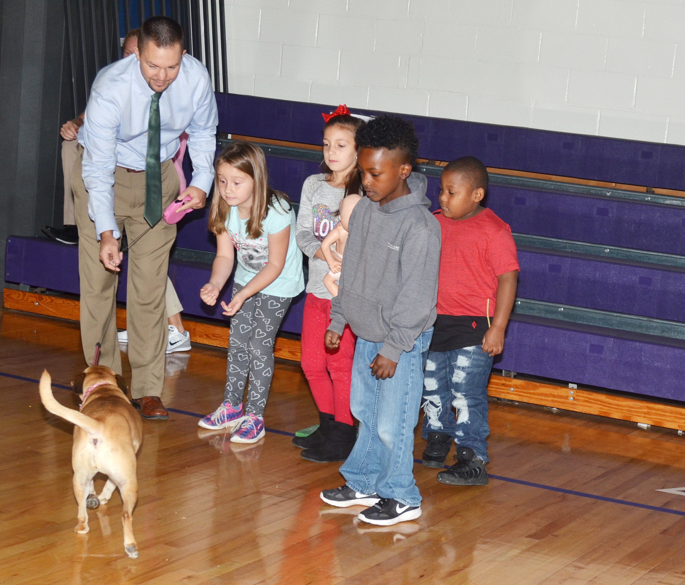CES Assistant Principal Weston Jones waits with CES students, from left, first-grader Natalee Shaw, second-graders Lillian Martin and Drelynn Hollins and first-grader Malachi Conner and the family dog as they show students the proper way to leave a home in case of a fire.