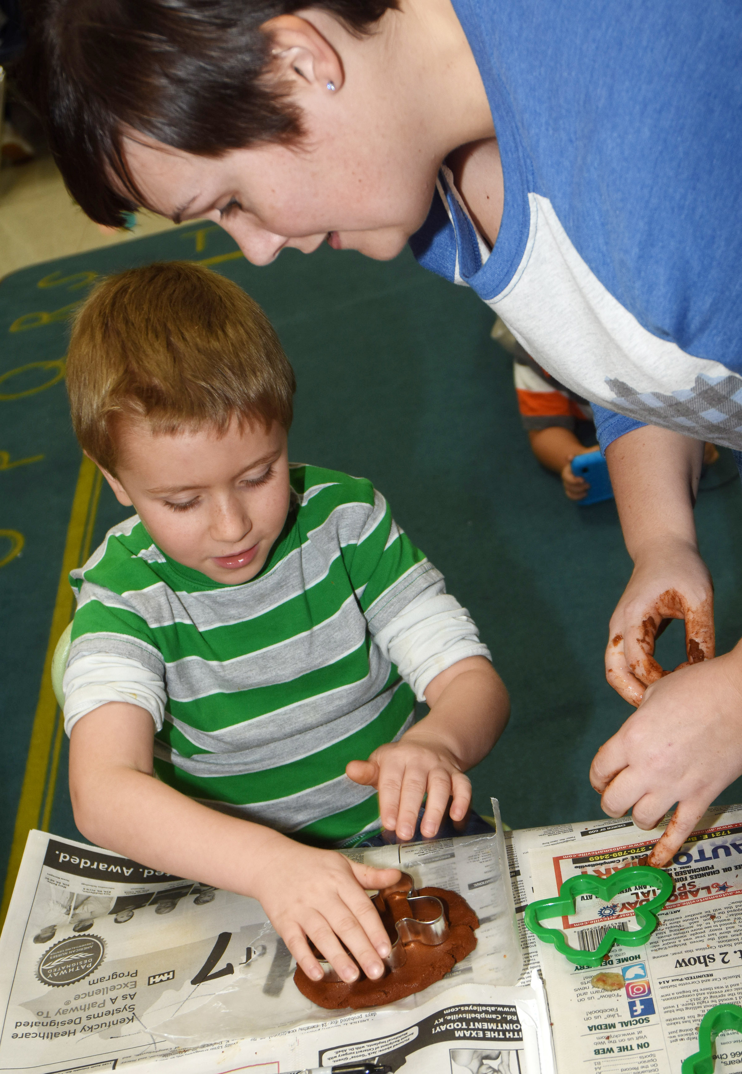 CES first-grader Alex Newcomb makes his gingerbread ornament, with help from teacher Amanda Barnett.