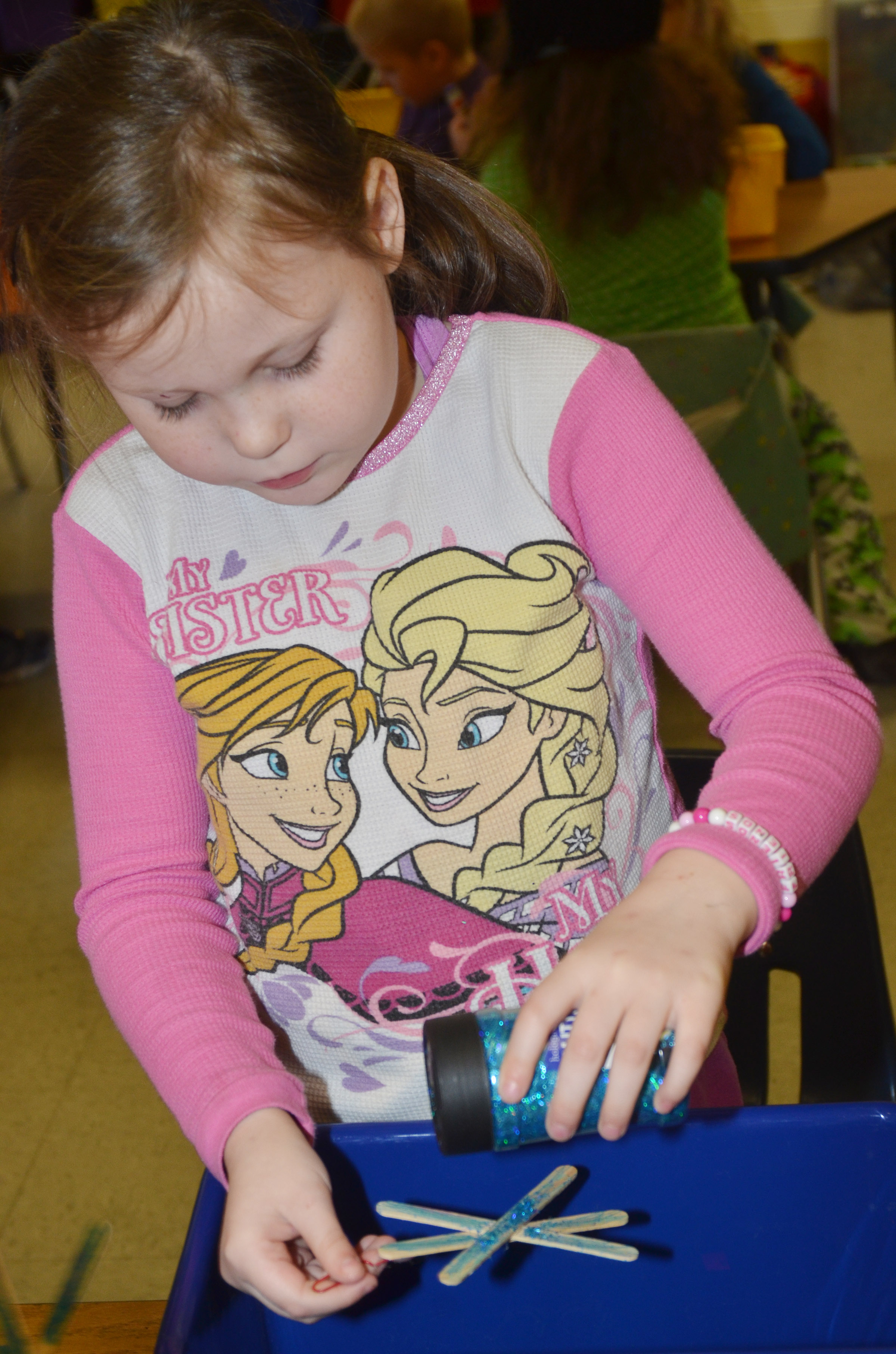 CES first-grader Cadynce Cox adds glitter to her snowflake ornament.