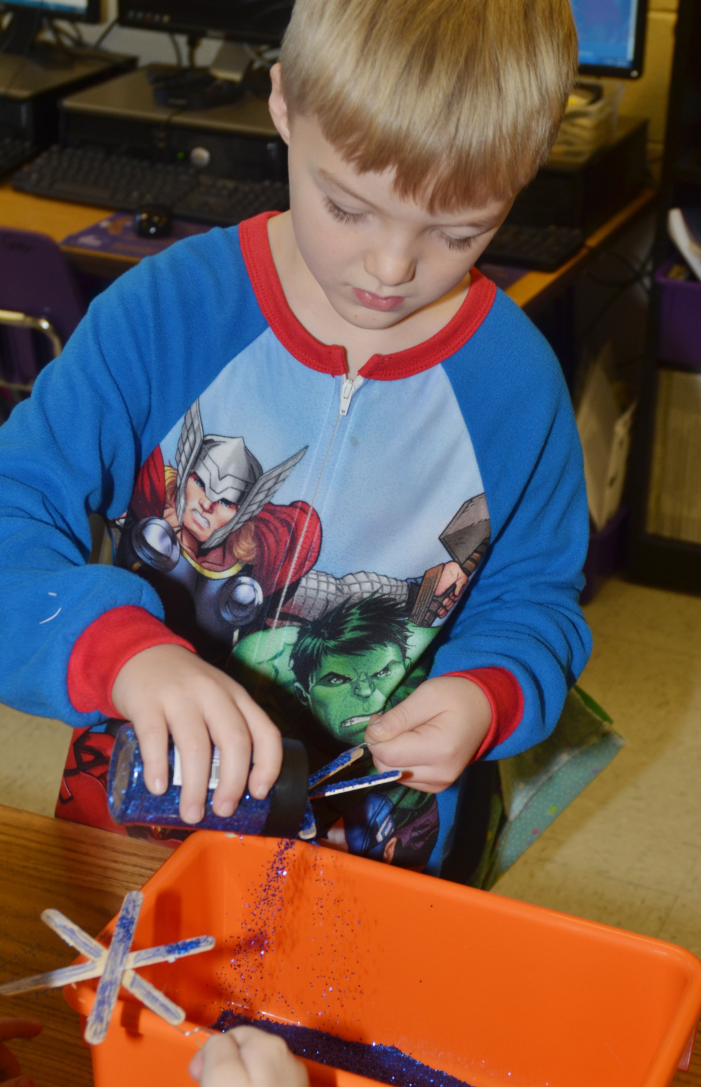CES first-grader Samuel Scharbrough adds glitter to his snowflake ornament.
