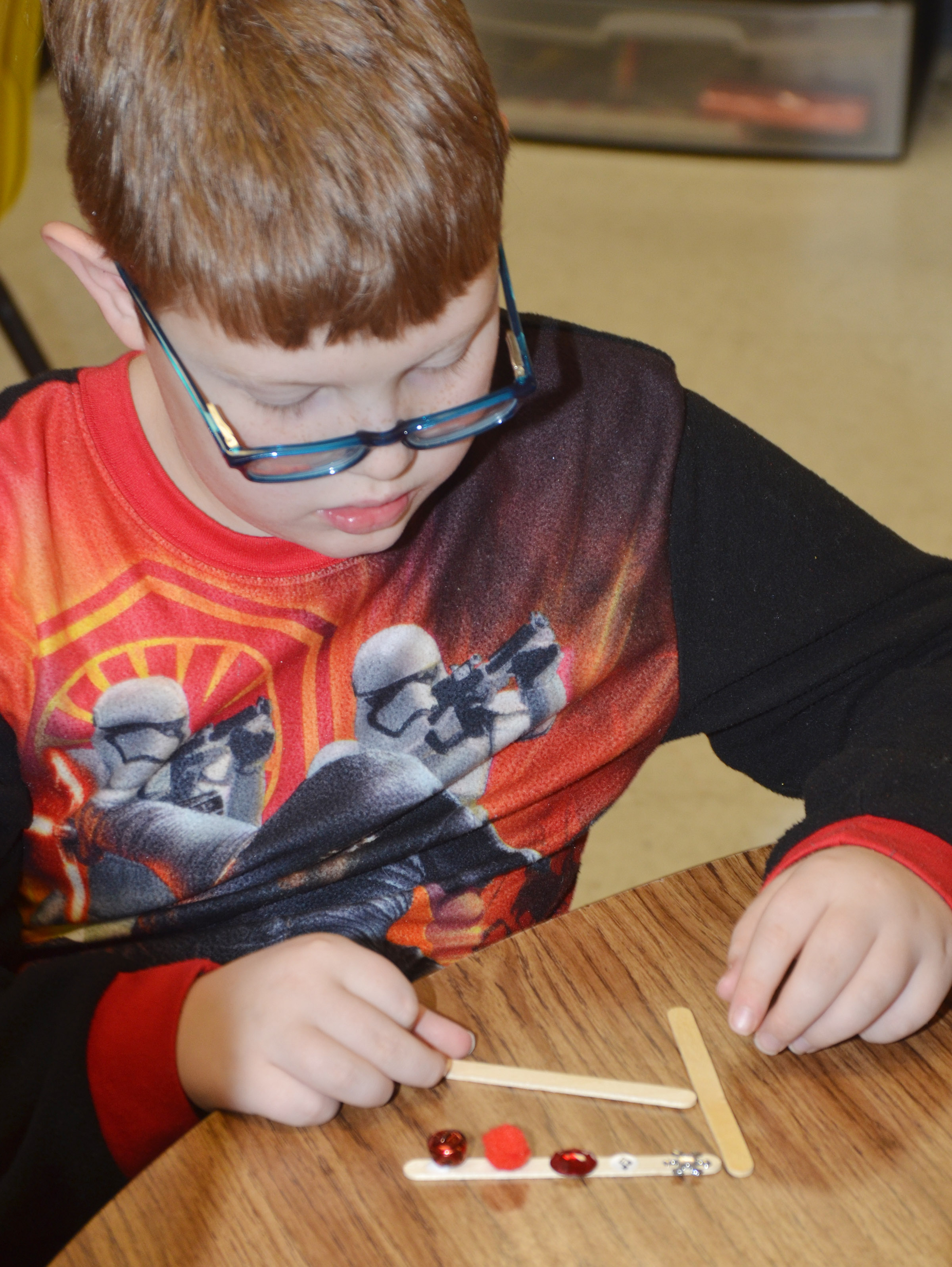 CES third-grader Aidan Phillips makes a snowflake ornament.