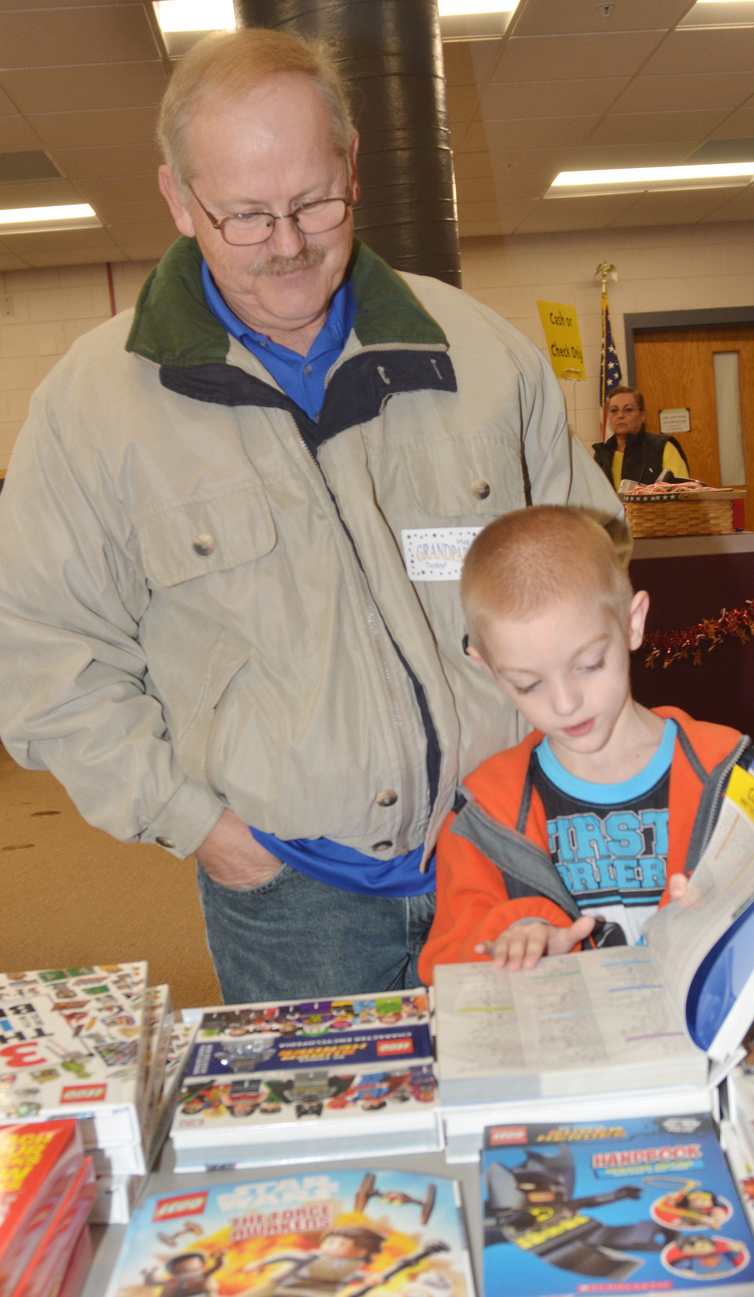 CES second-grader Evan Cundiff looks at books with his grandfather, Lynn Colvin.