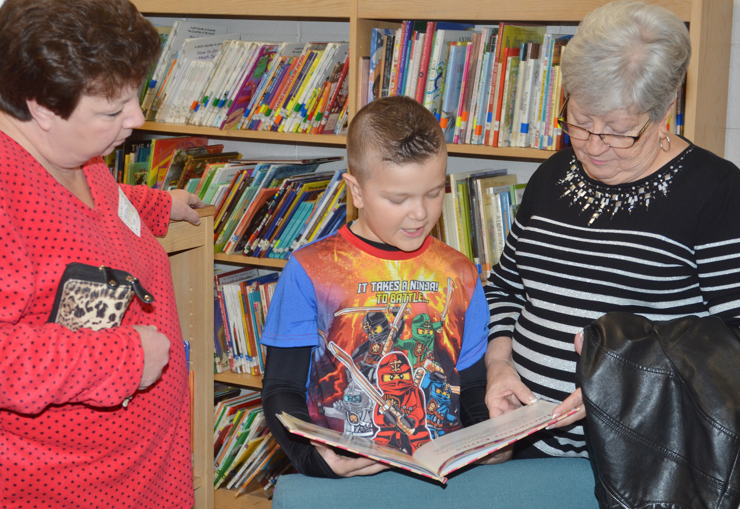 CES second-grader Cayton Lawhorn reads with his grandmothers, Jeanean Malone, at left, and Lillian Lawhorn.