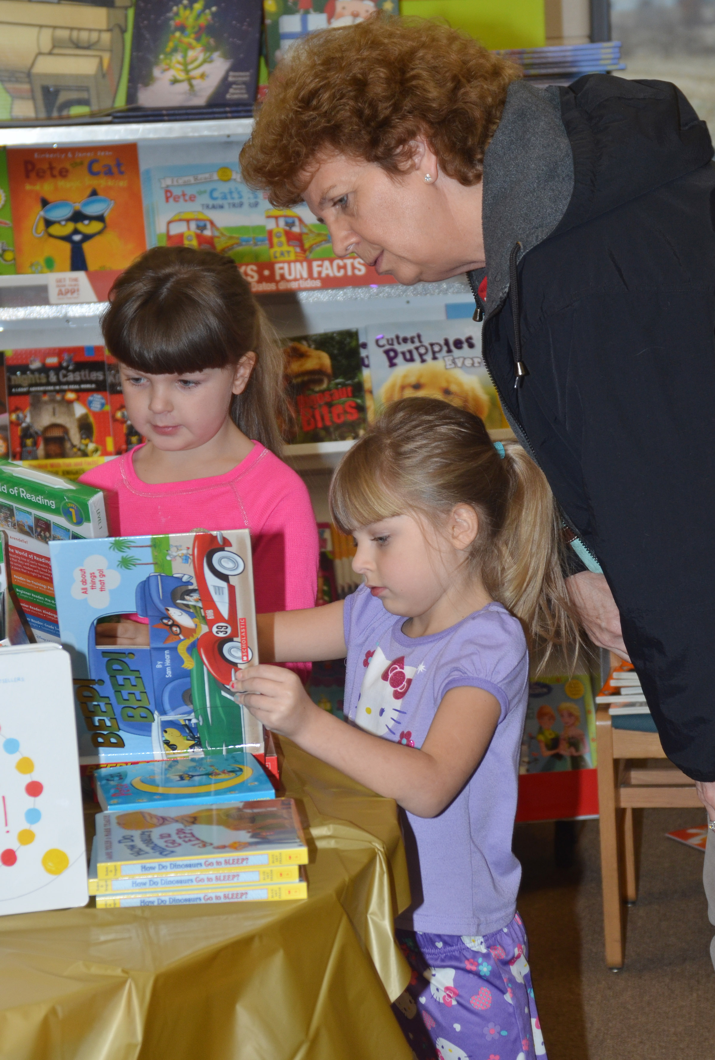 CES second-grader Kaleigh Wilhoite, at left, and her sister, kindergartener Madison Wilhoite, look at books with their grandmother, Trena Burchett.