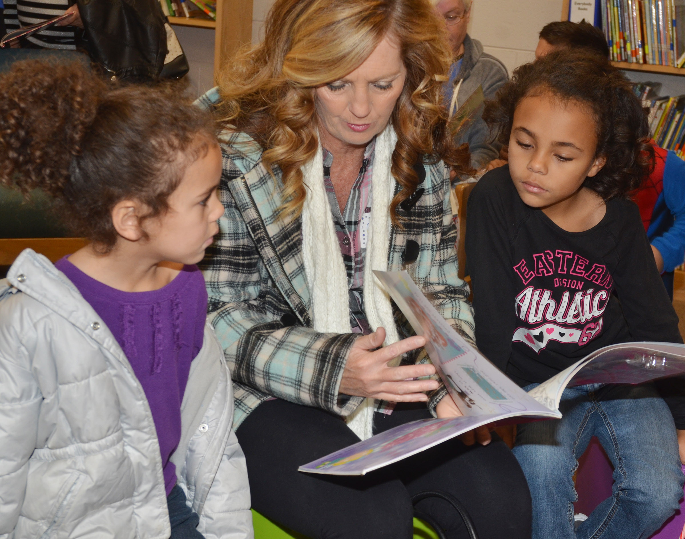 CES preschool student Adelyn Litsey, at left, and her sister, second-grader Braelyn Taylor, read with their grandmother, Sheila Stamp.