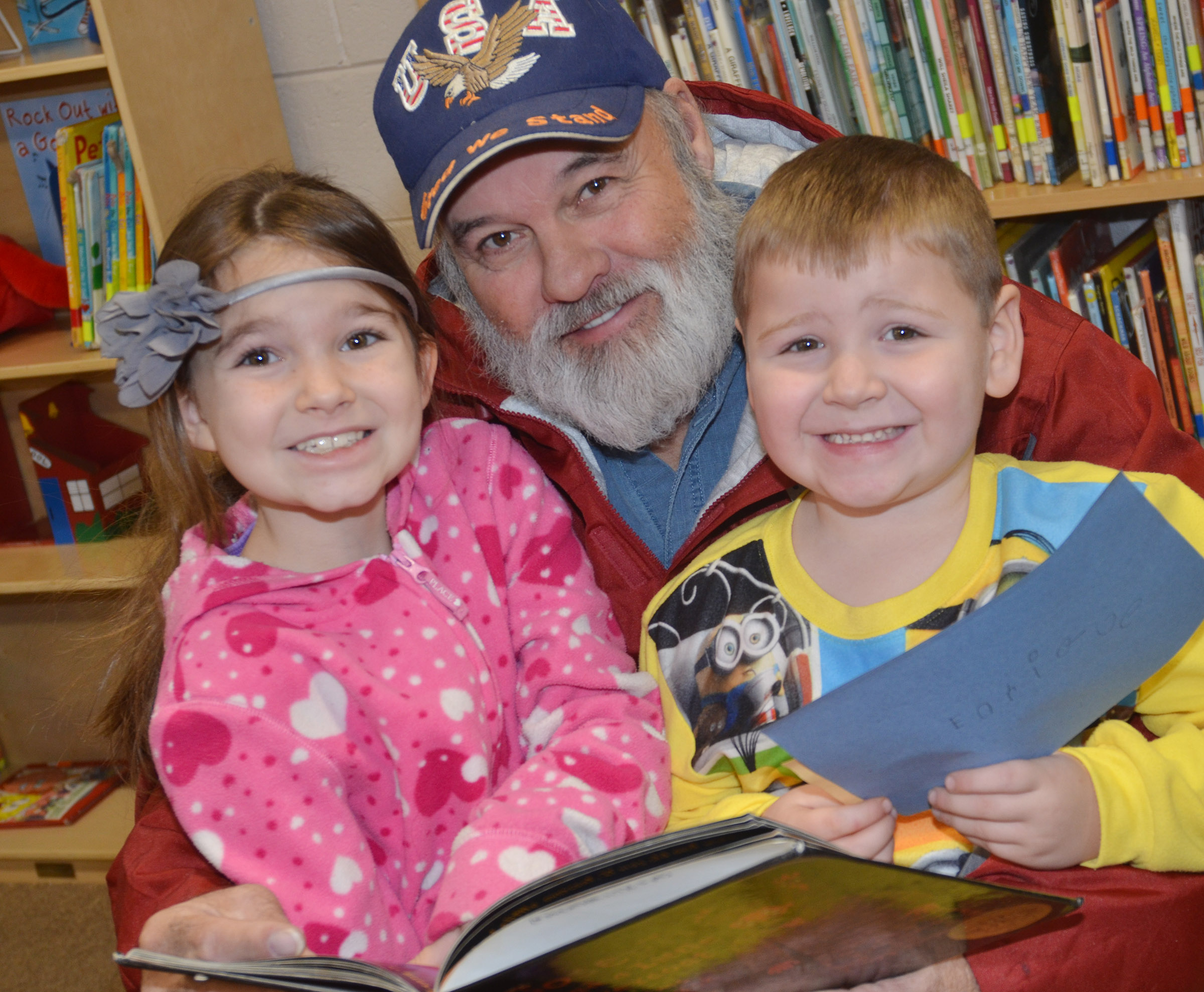 CES third-grader Destiny Abell, and her brother, kindergartener Enrique McDonald, read with their grandfather, Frank McDonald.