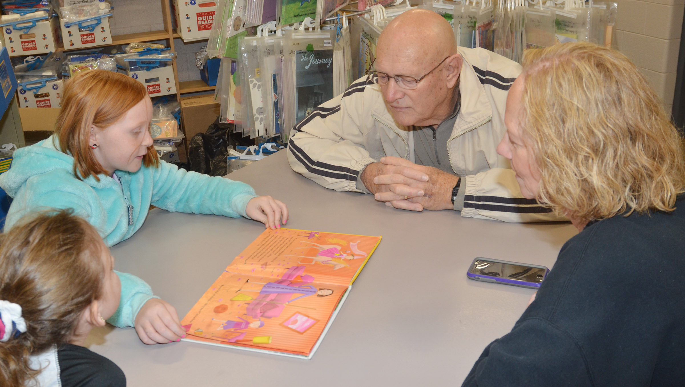 CES third-grader Nora Harris reads with her grandparents, Paul and Lois Lacy.