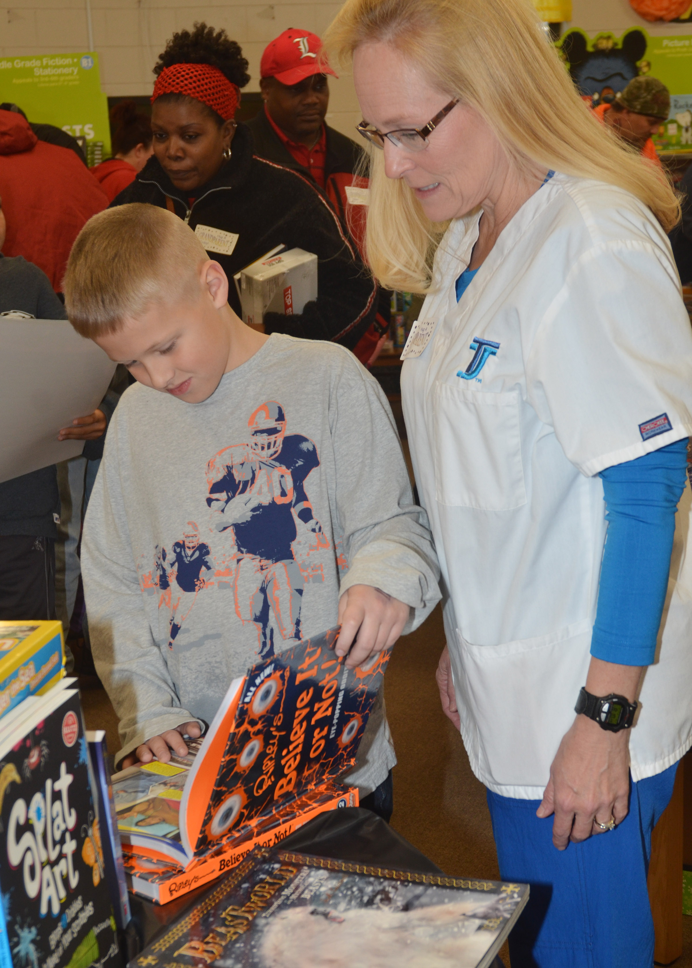 CES second-grader Evan Lockridge looks at books with his grandmother, Karen Hall.