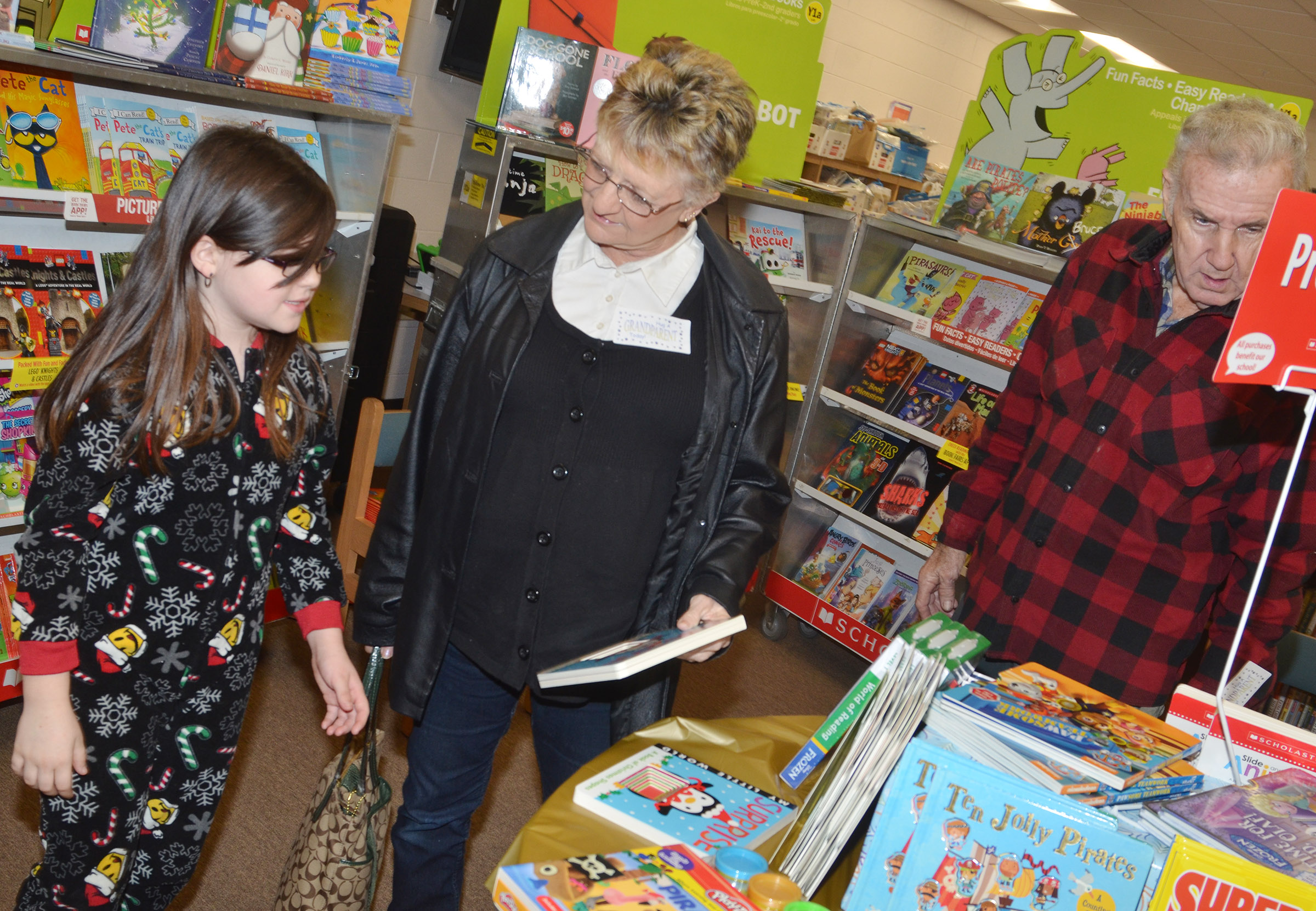 CES third-grader Lauren Pace shops the book fair with her grandparents.