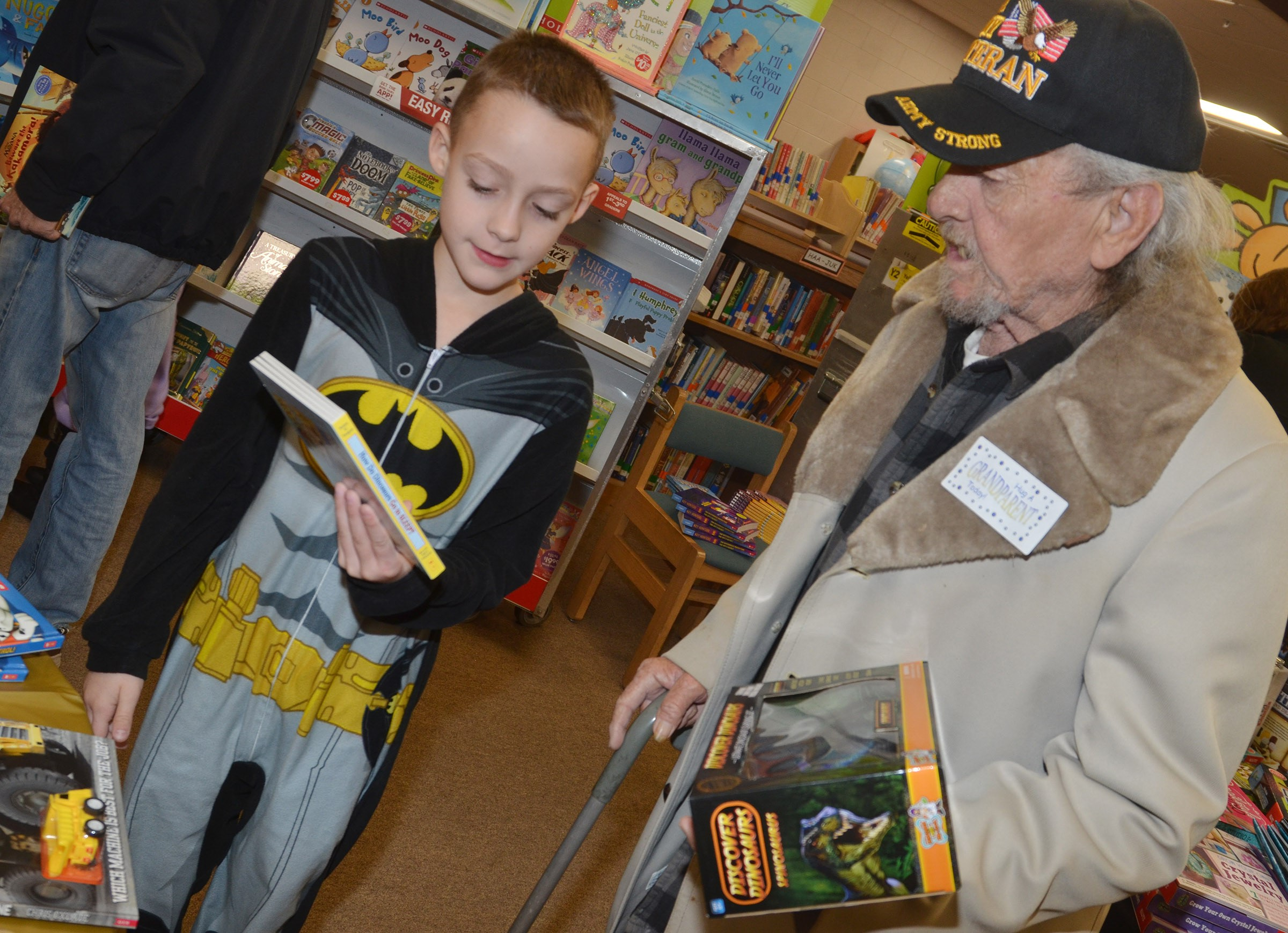 CES third-grader Caysen Tungate looks for books with his grandfather, John Mascarenas.
