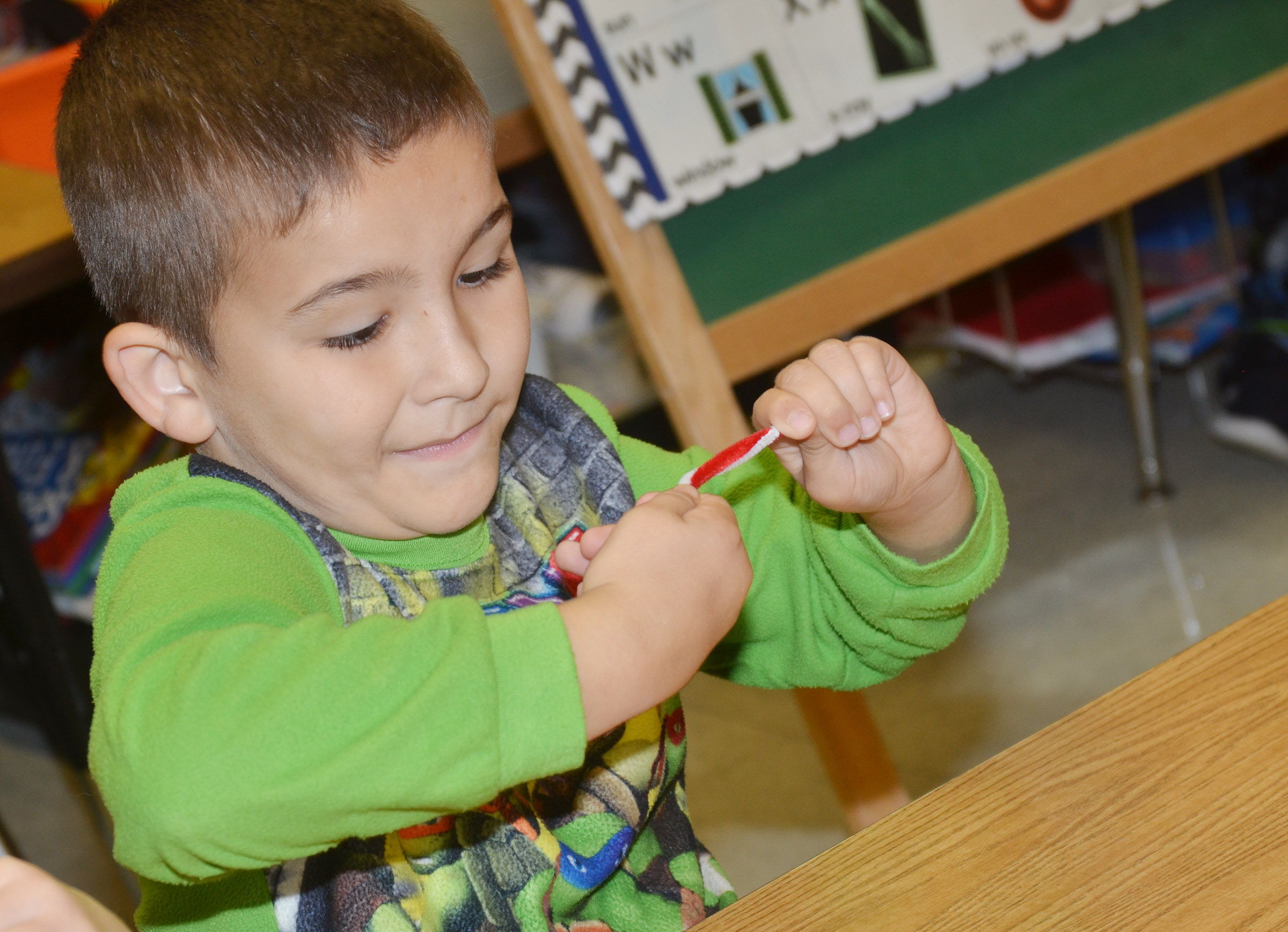 CES second-grader Josiah Edwards makes his candy cane ornament.