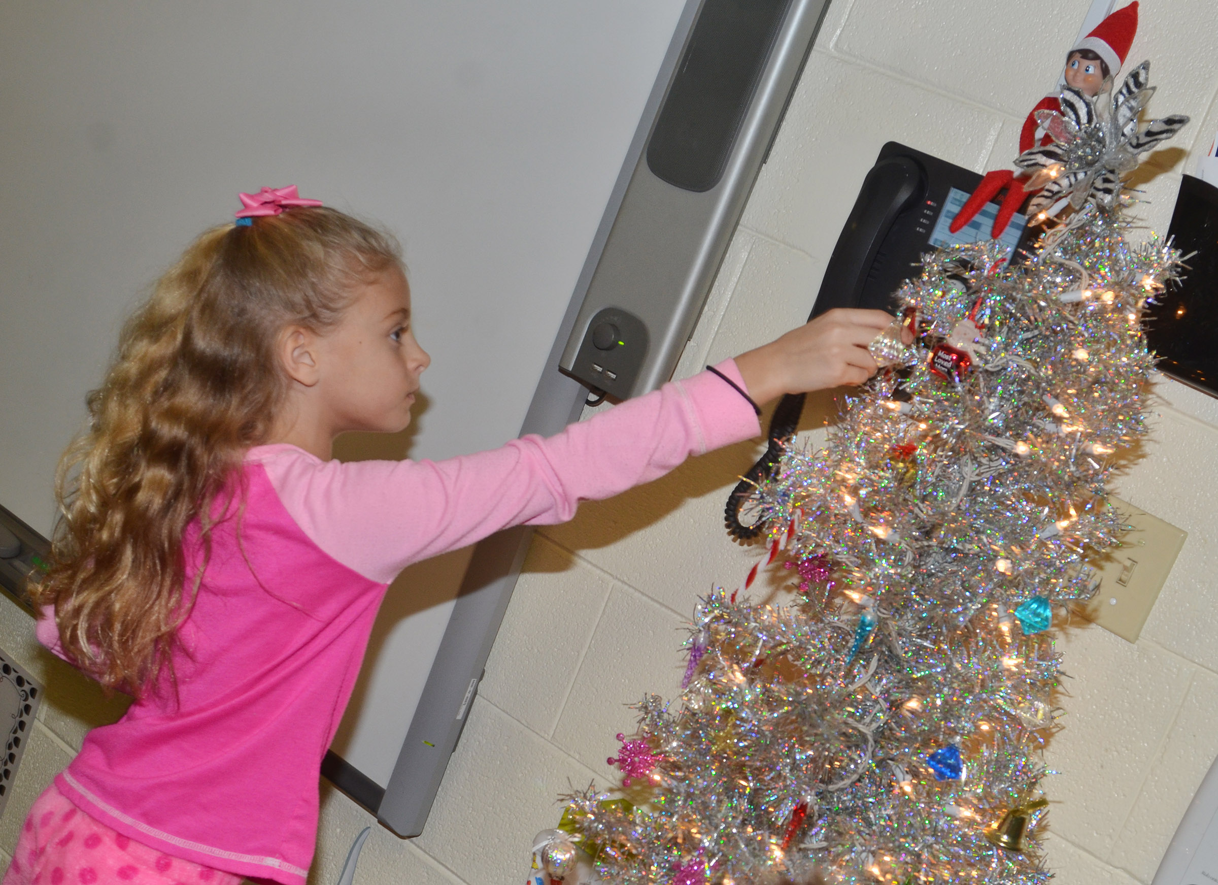 CES second-grader Aliyah Litsey hangs her ornament on the class tree.
