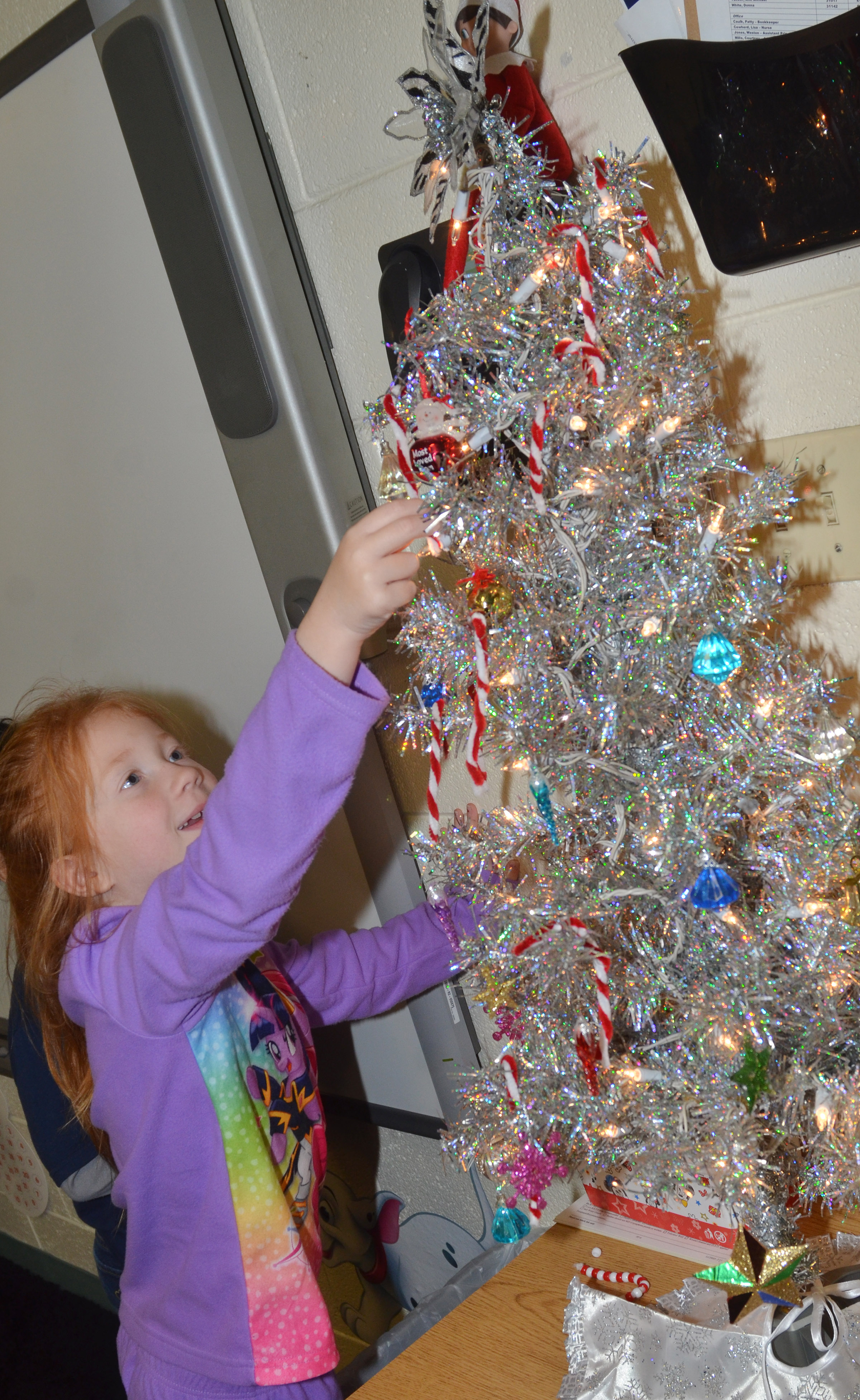 CES second-grader Bella Stout hangs her ornament on the class tree.