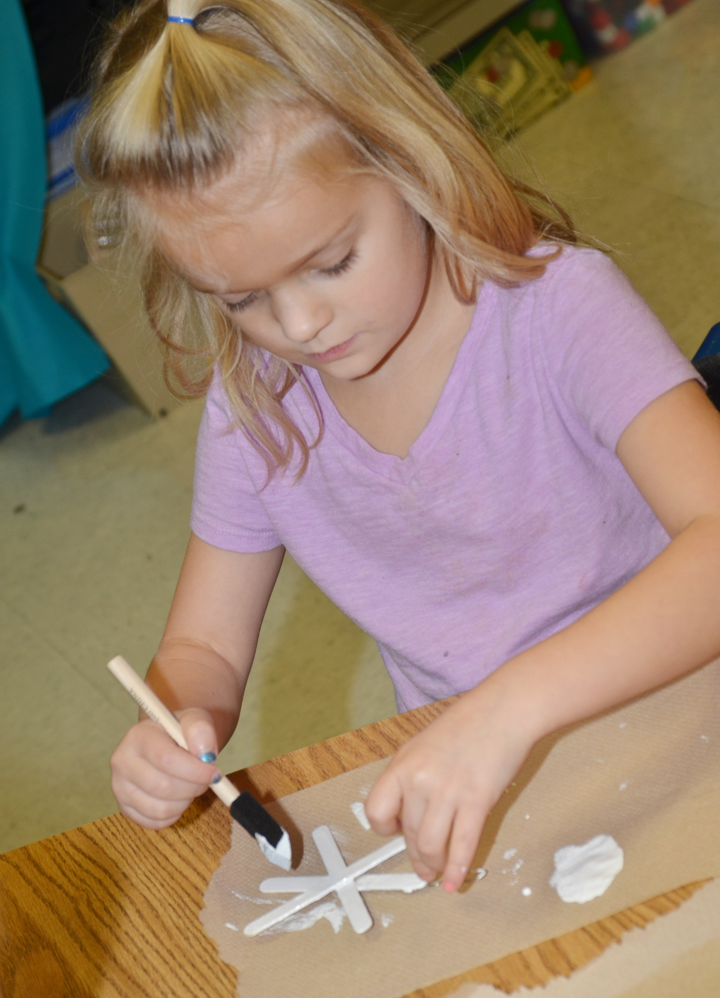 CES second-grader Miley Orberson paints her snowflake ornament.