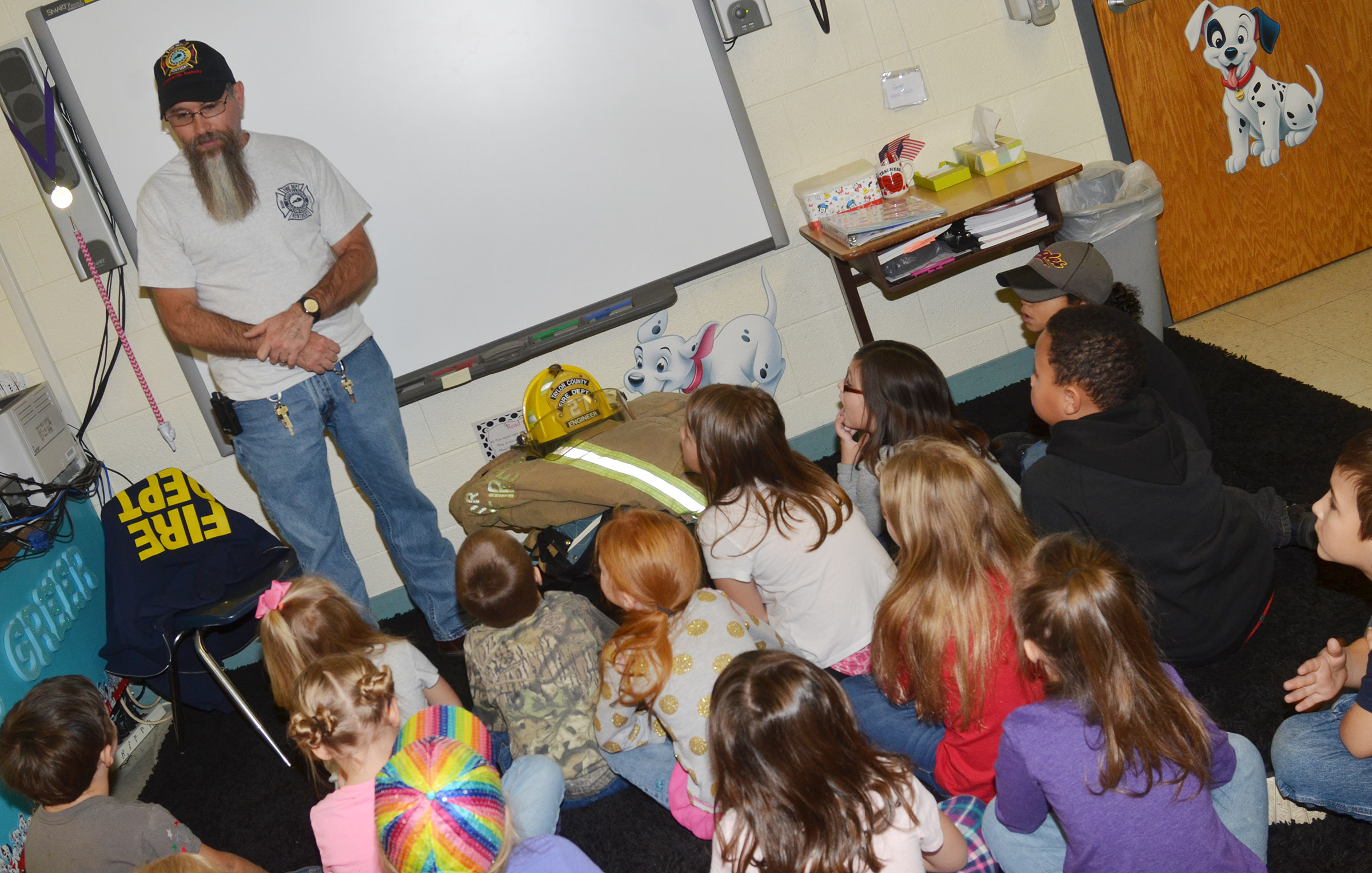 Randy Bricken, who is a volunteer firefighter at Taylor County Fire & Rescue and a custodial worker at Campbellsville elementary, middle and high schools, talks to CES first-graders about why it's important to help others.