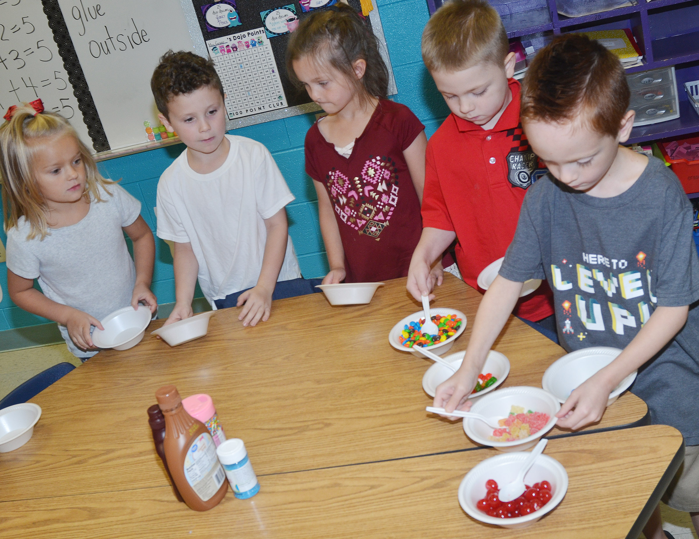 CES first-grader Carson Montes gets gummy bears for his ice cream sundae, as his classmates, from left, Miley Orberson, Braydan Dyer, Addison Perkins and Noah Milburn wait their turn.