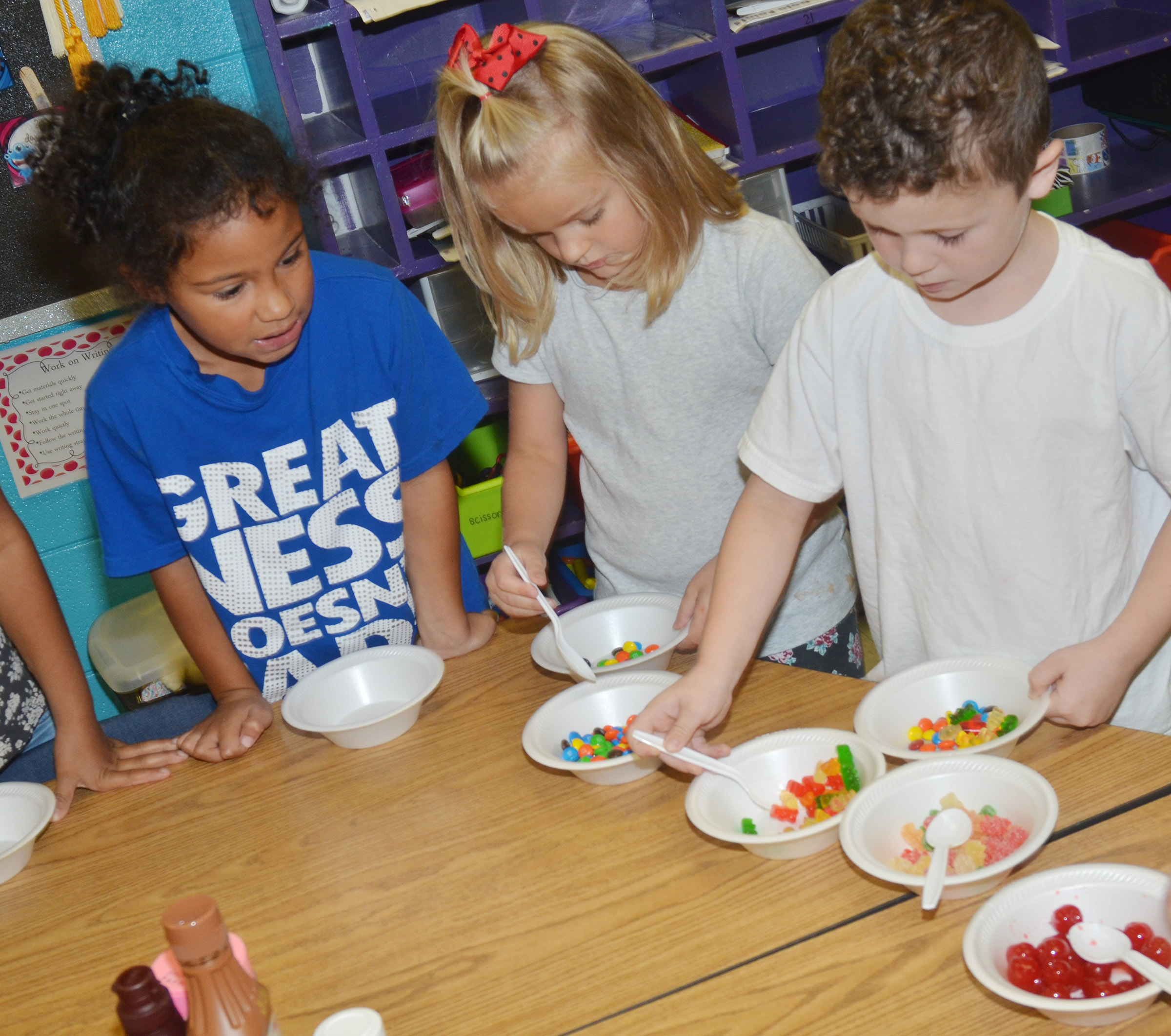 From left, CES first-graders Nevaeh Shofner, Miley Orberson and Braydan Dyer get toppings for their ice cream sundaes.