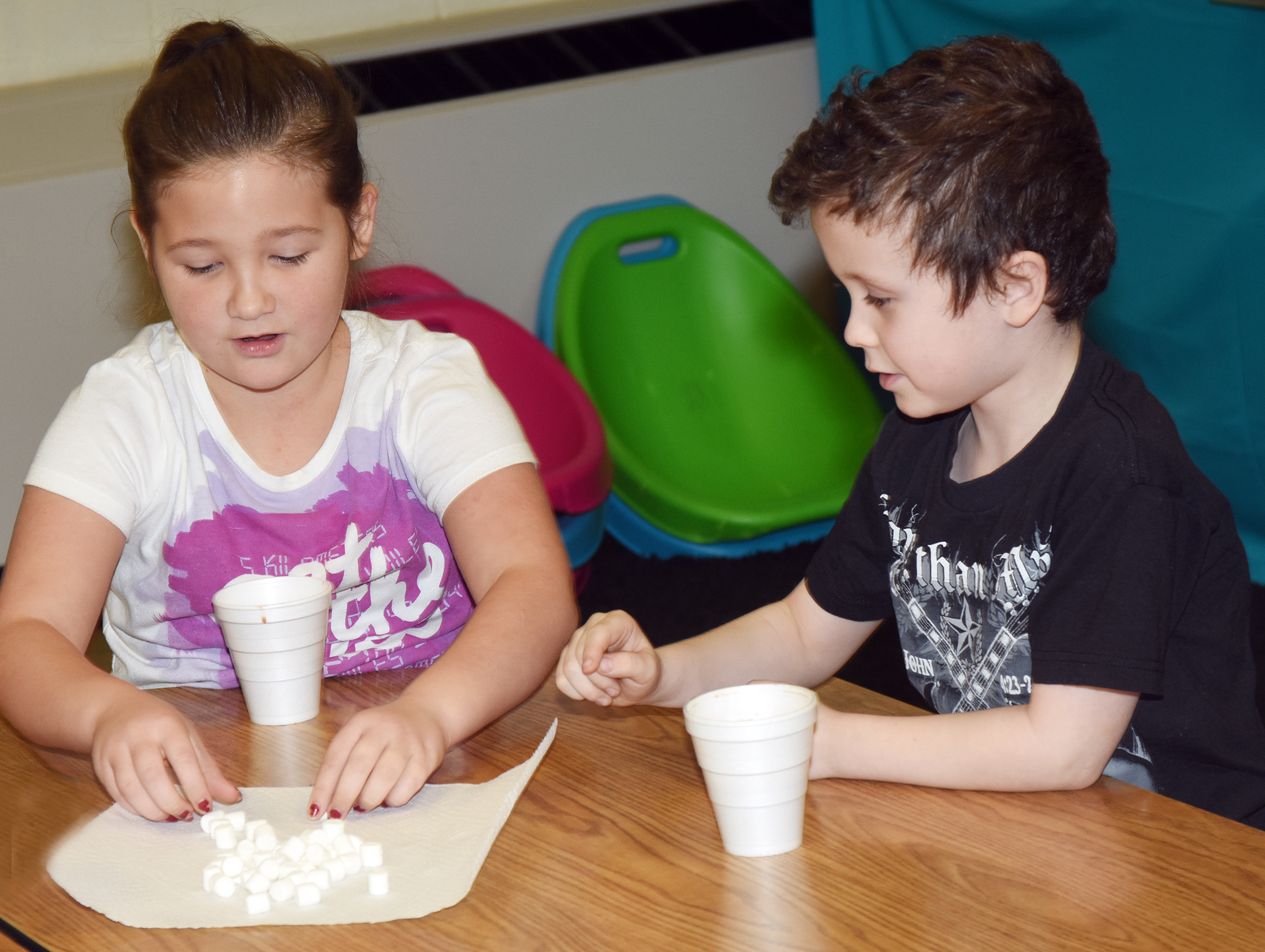 CES first-graders Destiny Rhinehart, at left, and Braydan Dyer add marshmallows to their hot chocolate.