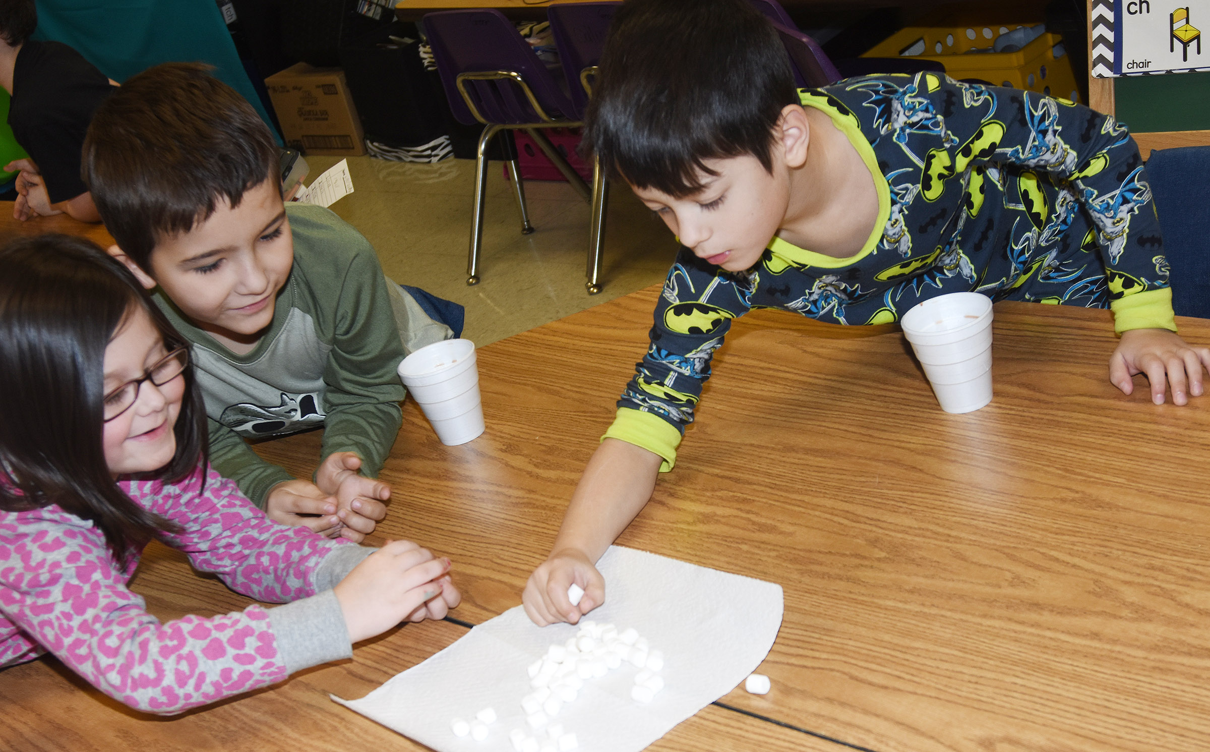 From left, CES first-graders Trinity Clark, Josiah Edwards and Abram Adkins add marshmallows to their hot chocolate.