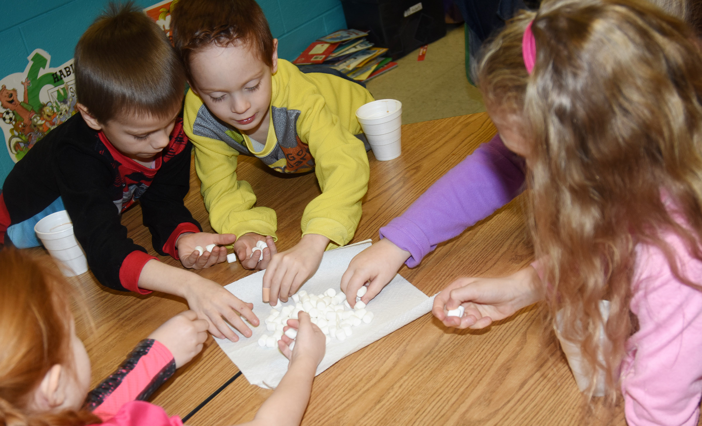 CES first-graders Alex Eggers, at left, and Carson Montes and their classmates add marshmallows to their hot chocolate.