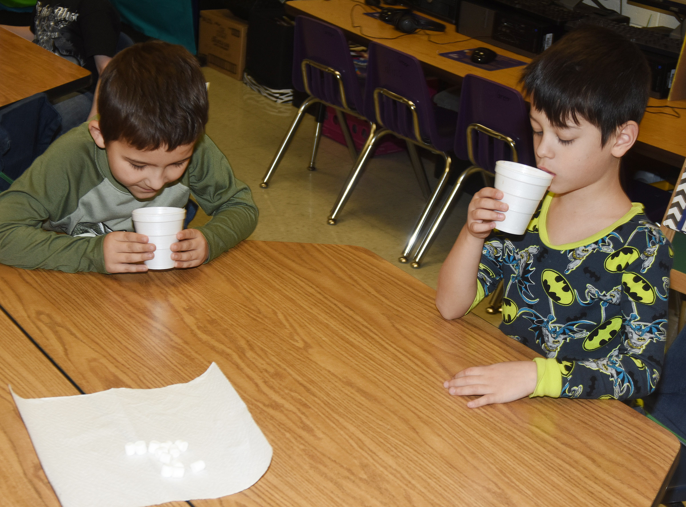 CES first-graders Josiah Edwards, at left, and Abram Adkins sample their hot chocolate.