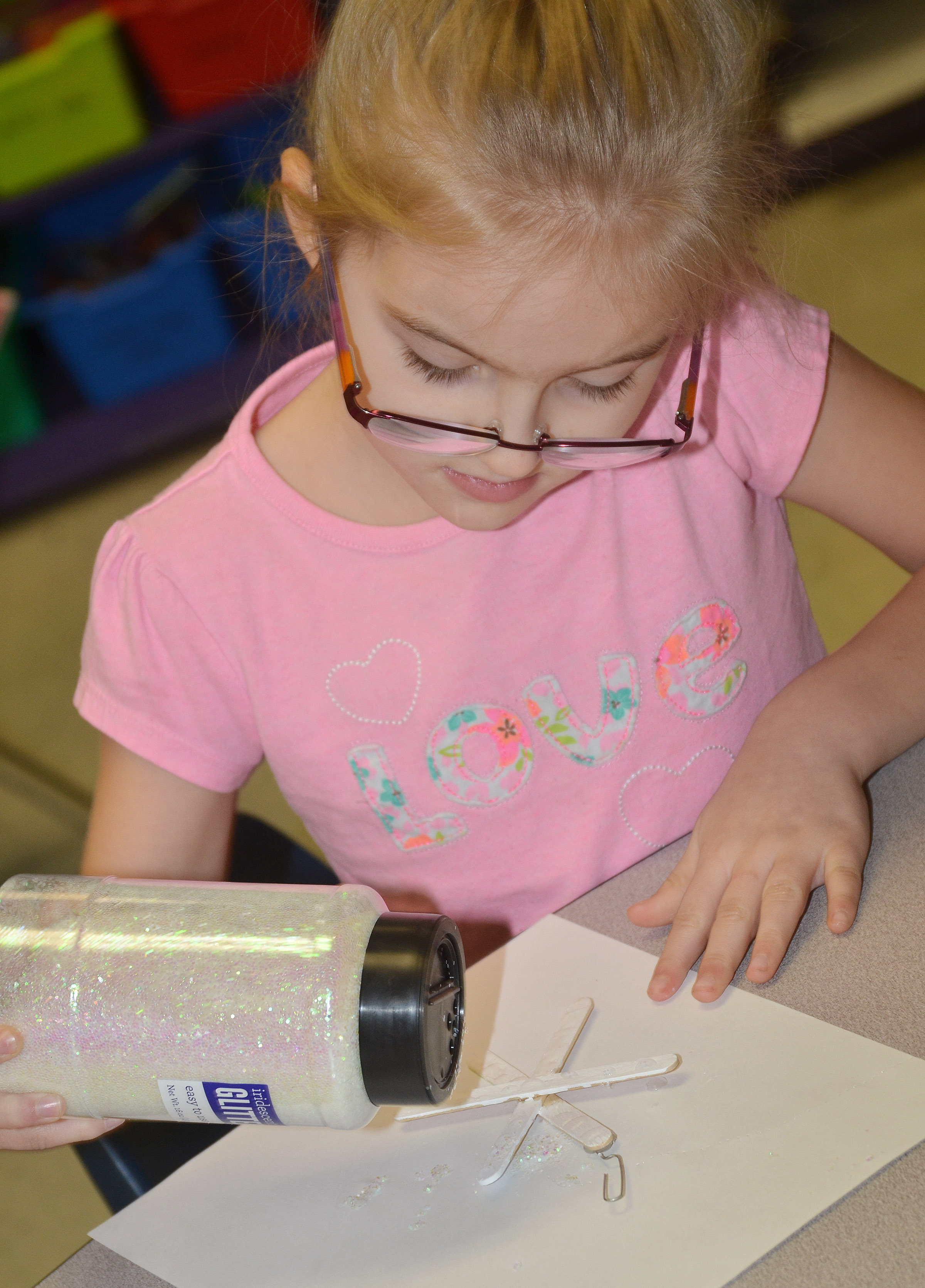 CES first-grader Jaden Lutz adds glitter to her snowflake ornament.