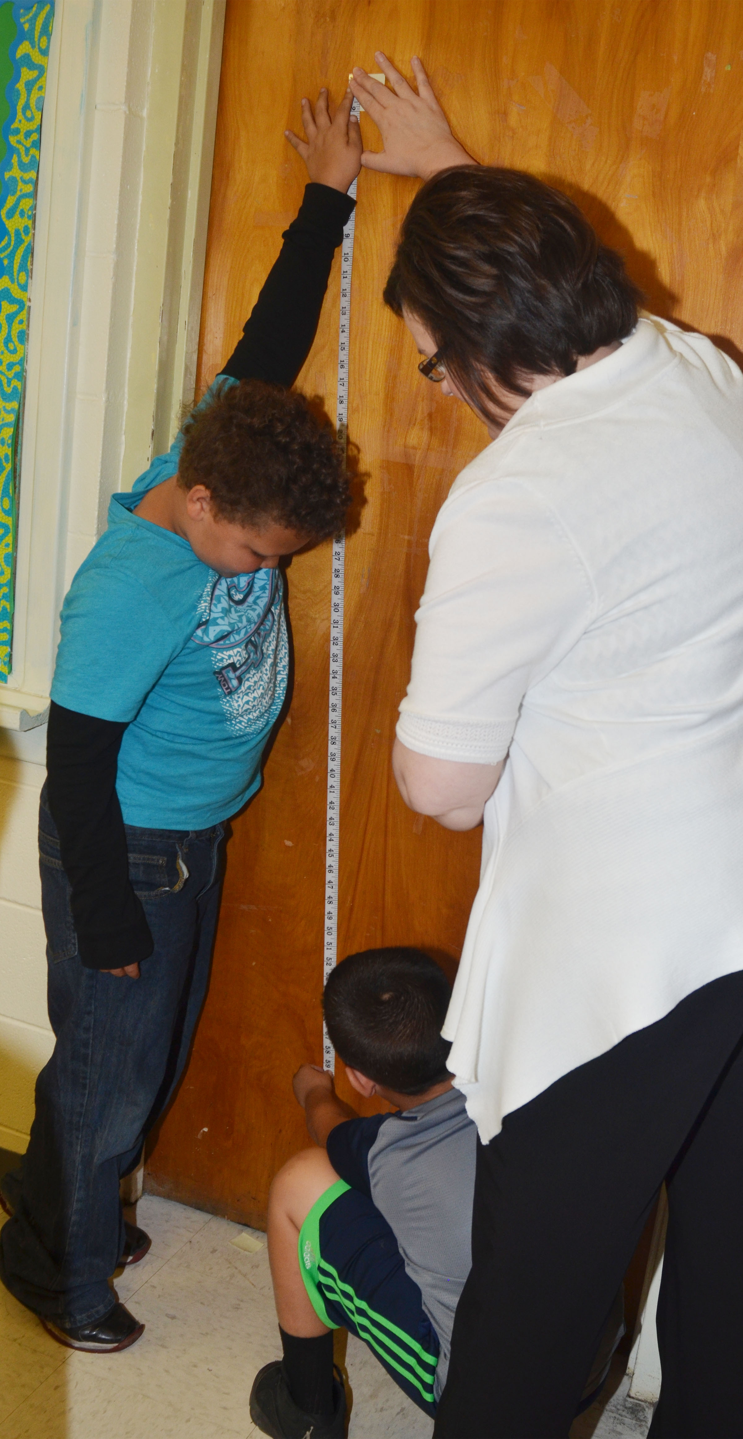 CES second-grade teacher Tonya Hagan helps Drevonte Gurley, at left, and Damien Clark record a measurement.